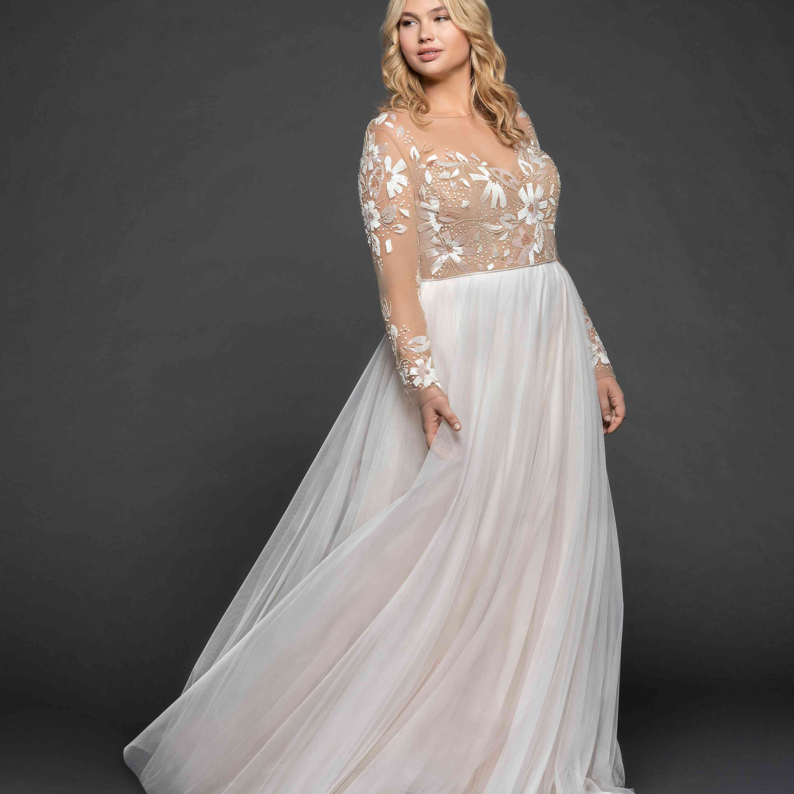 Plus size model in wedding gown with floral embellished illusion bodice