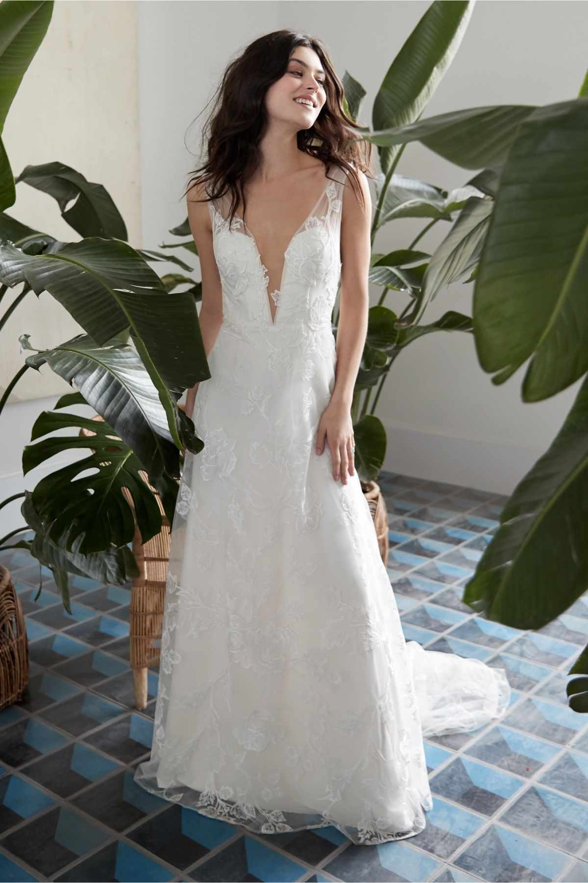 Model in allover lace deep V-neck A-line gown