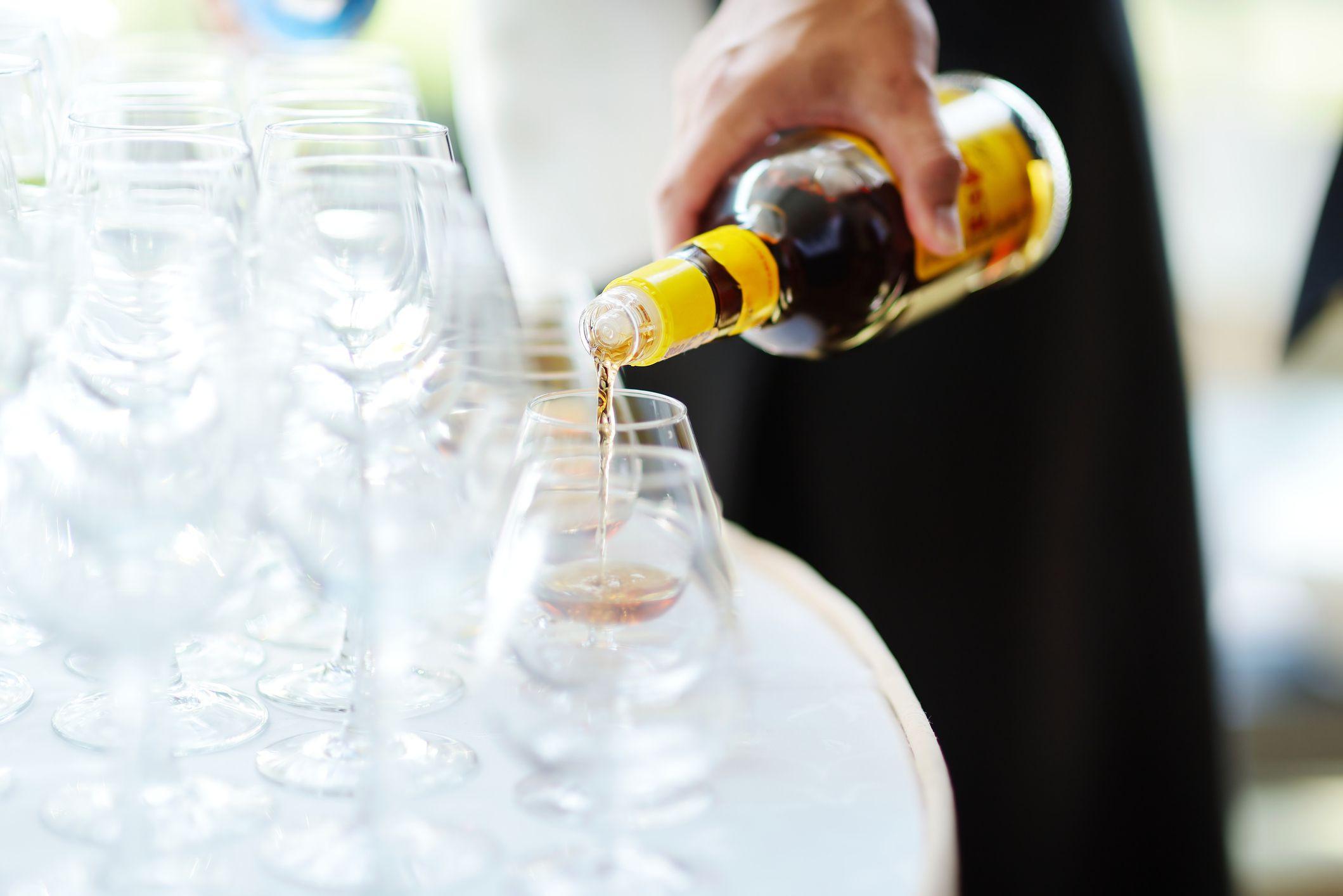 Hand pouring liquor into glasses