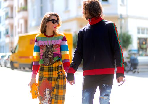 man and woman holding hands walking down the street