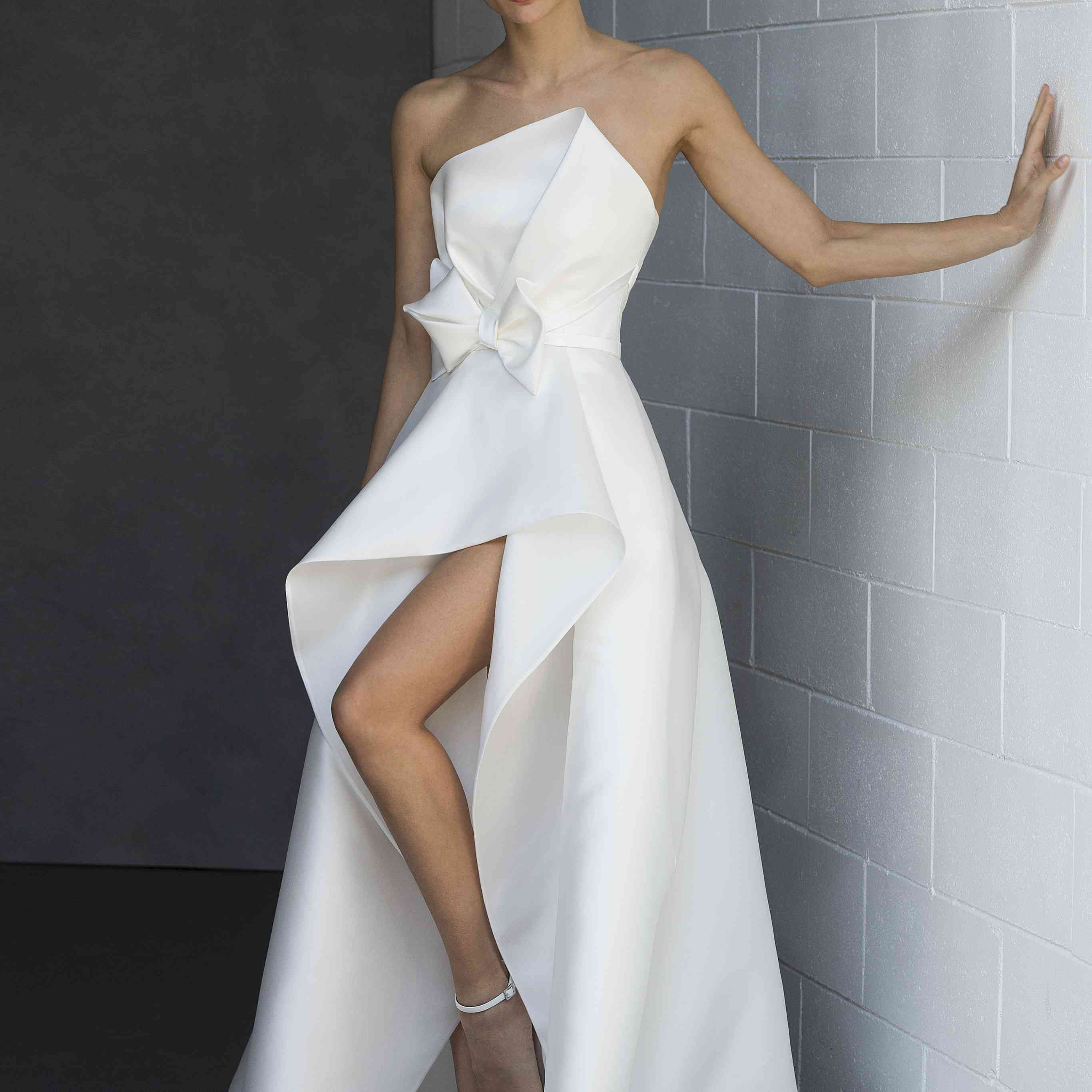 Model in strapless high-low gown with bow detail at the waist