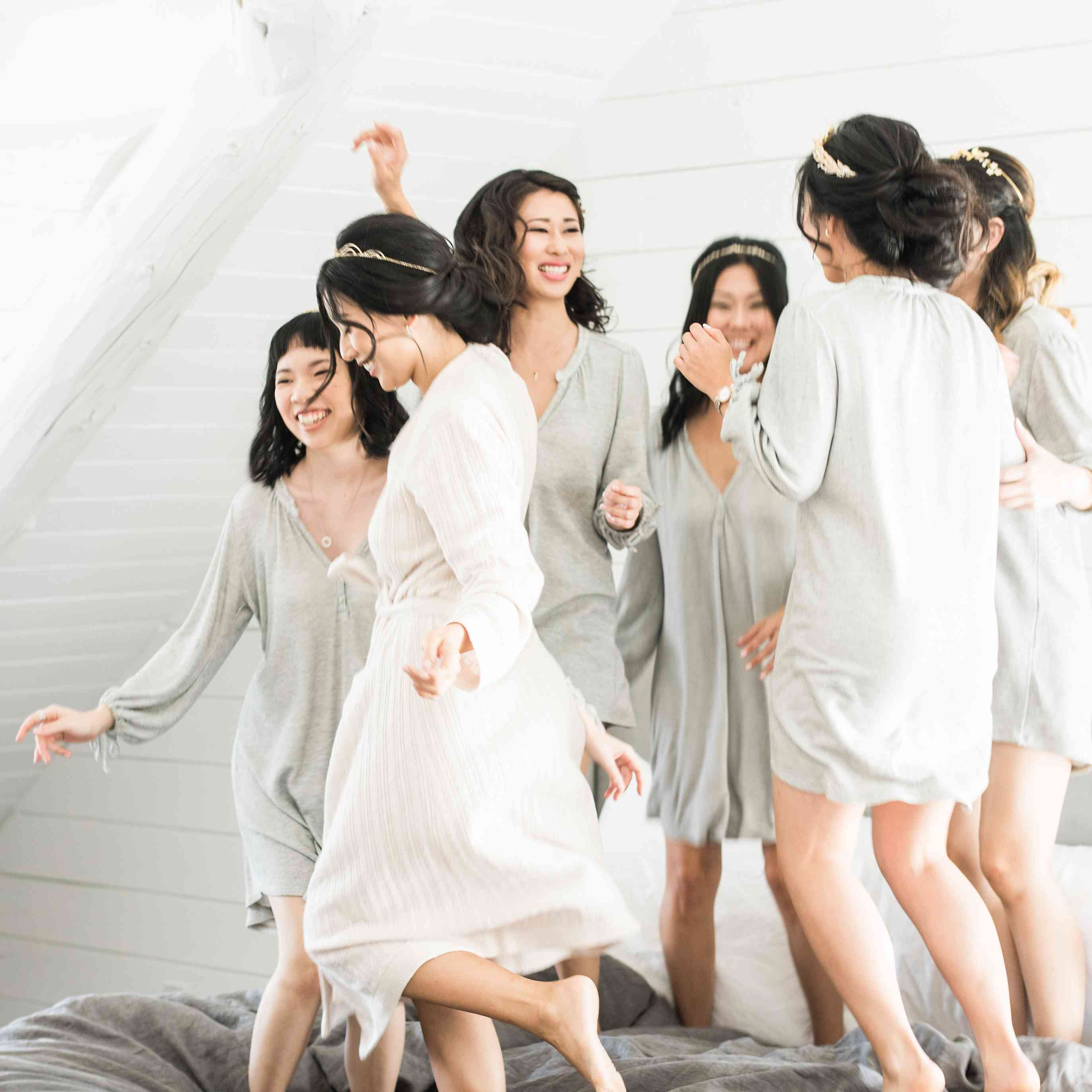 Bride Jumping on Bed With Bridesmaids