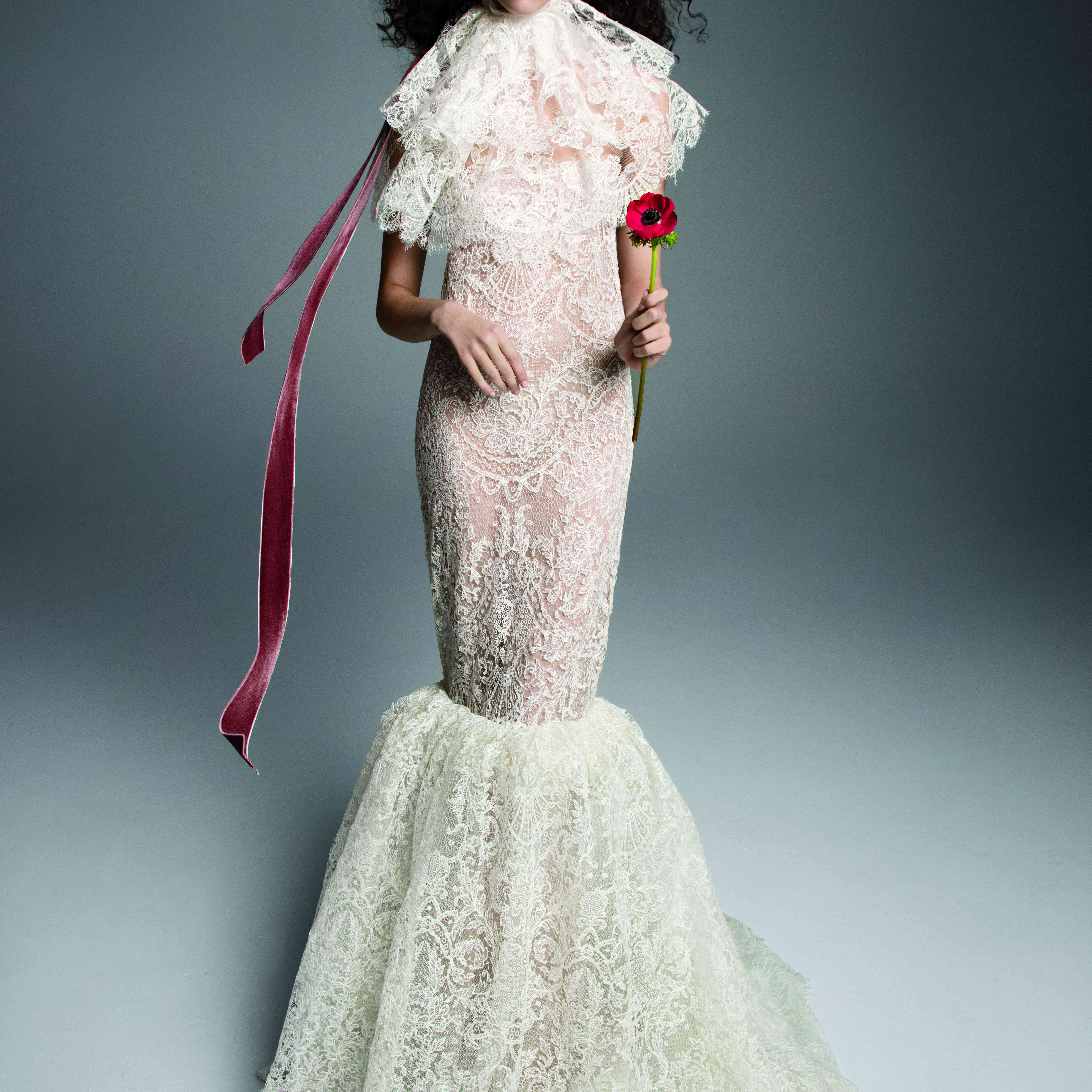 Model in allover lace mermaid gown with a red ribbon detail at the back neckline