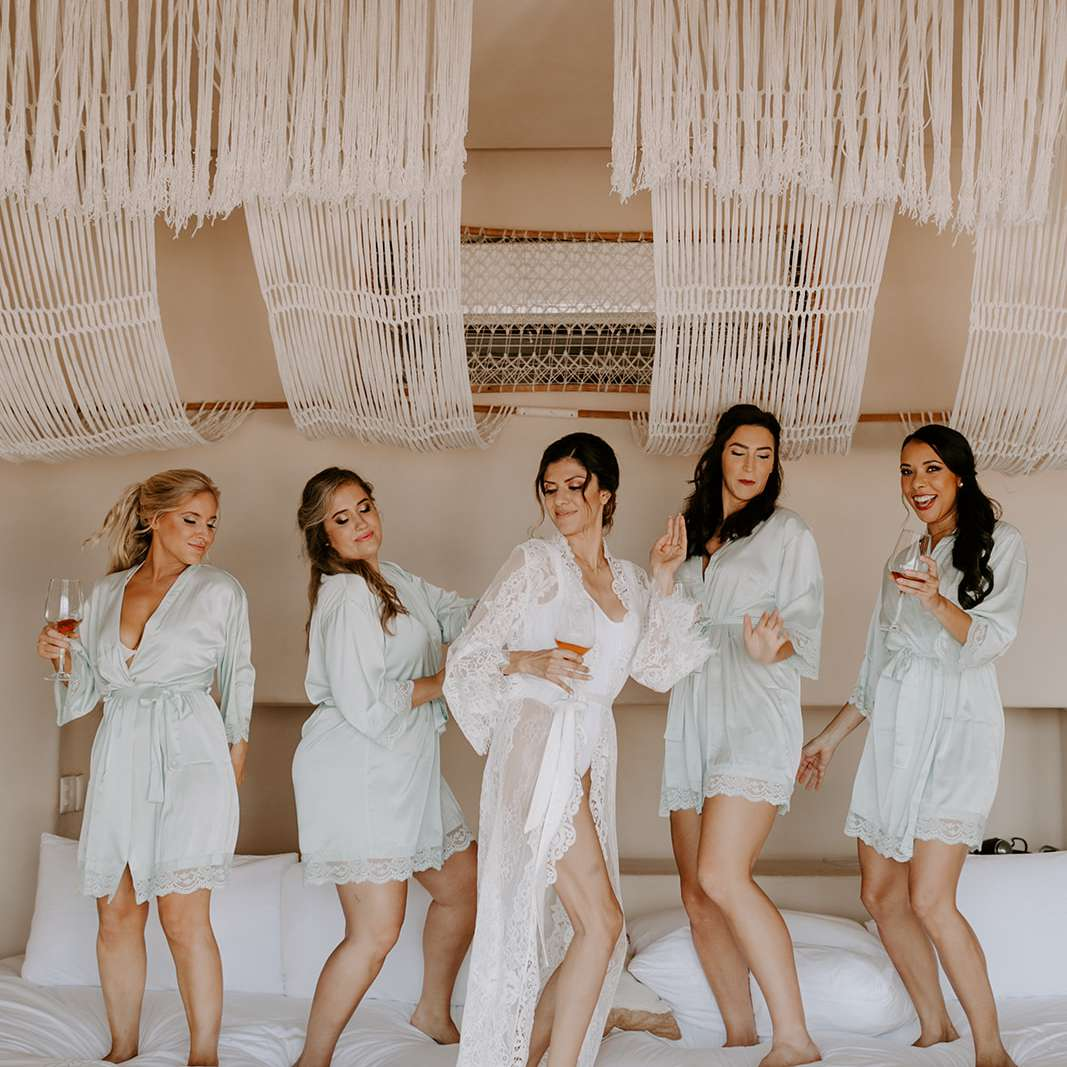 Girls in robes dancing on bed