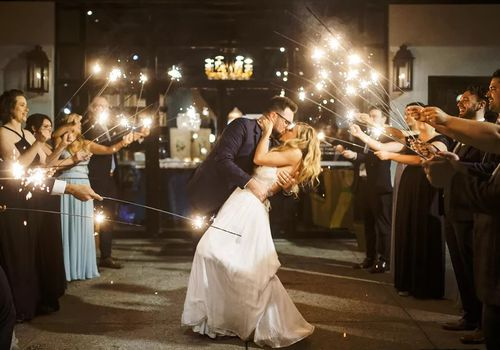 Couple kissing during sparkler exit