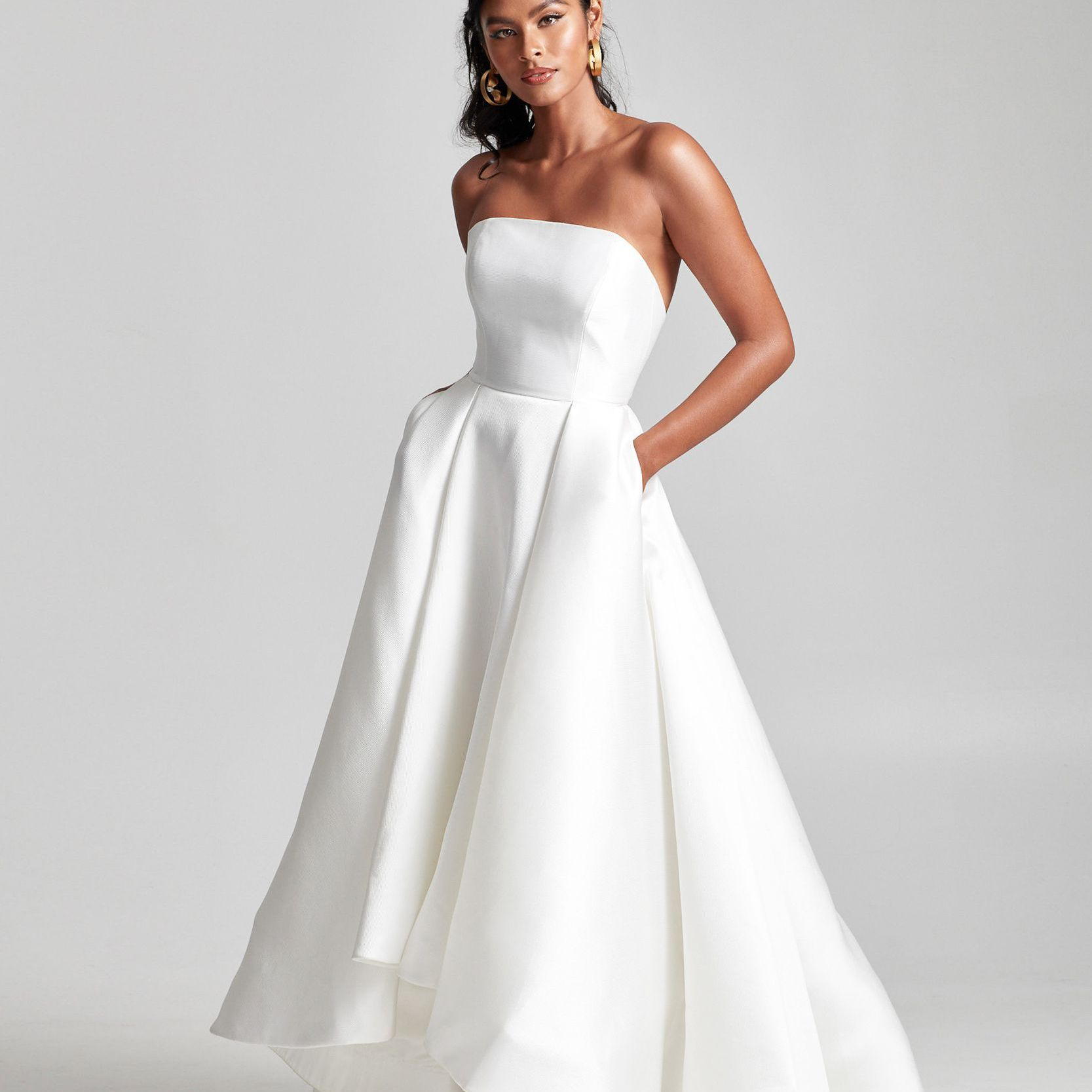 Model in strapless wedding gown with high-low skirt with pockets