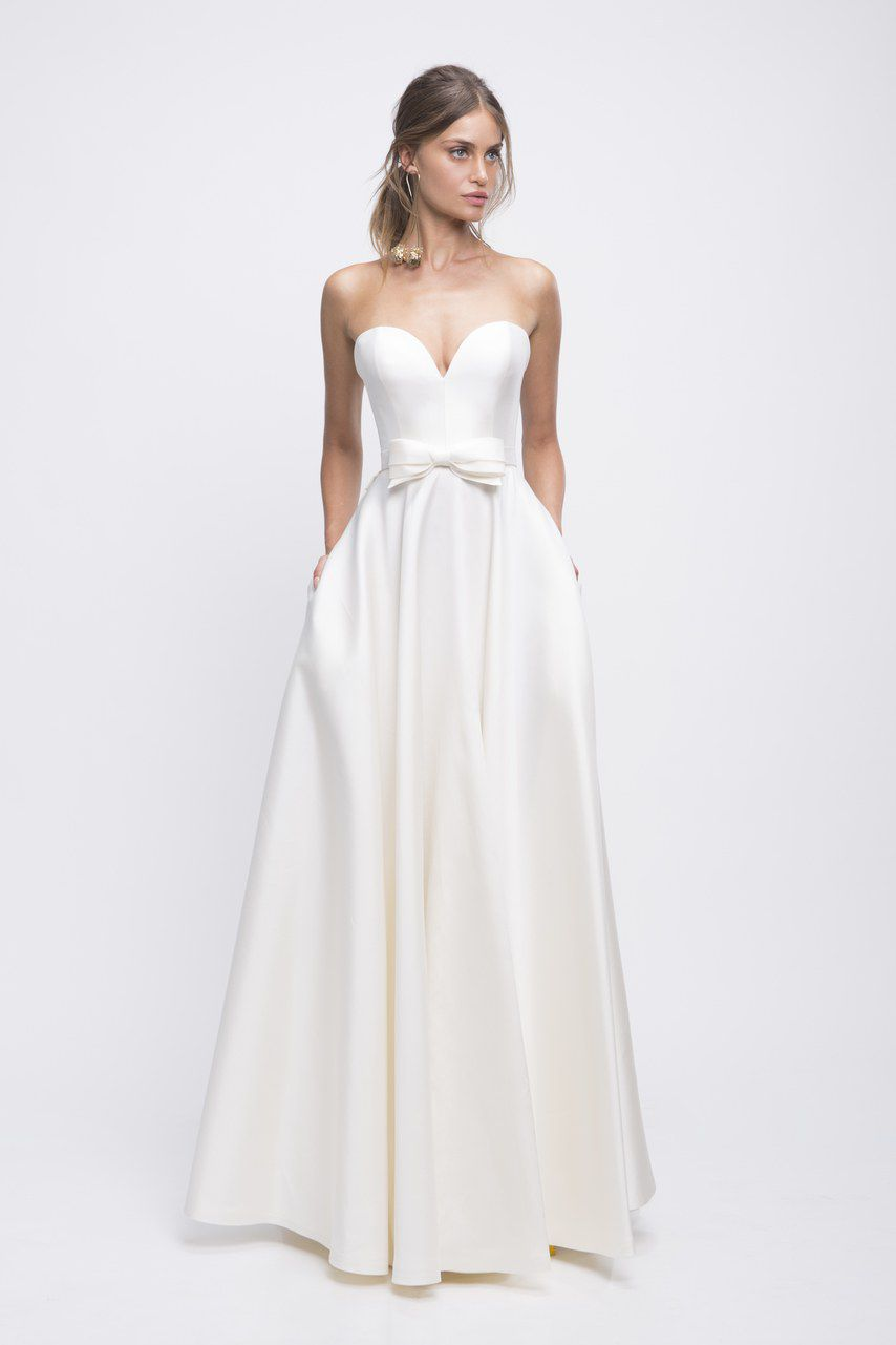 Model in strapless white wedding gown with bow detail at the waist