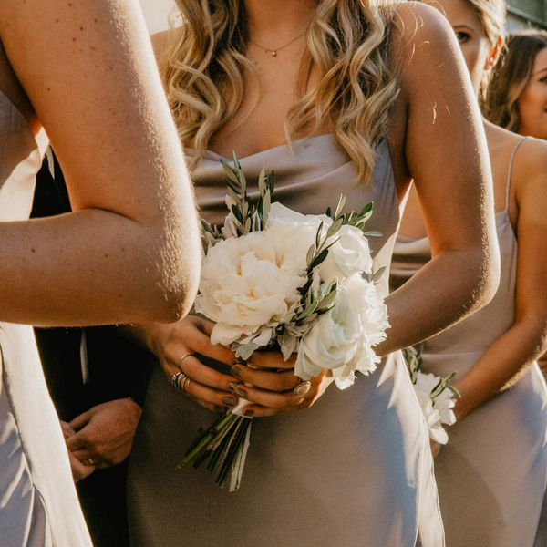 Close-up of bridesmaid in taupe dress holding a white bouquet with taupe nail polish