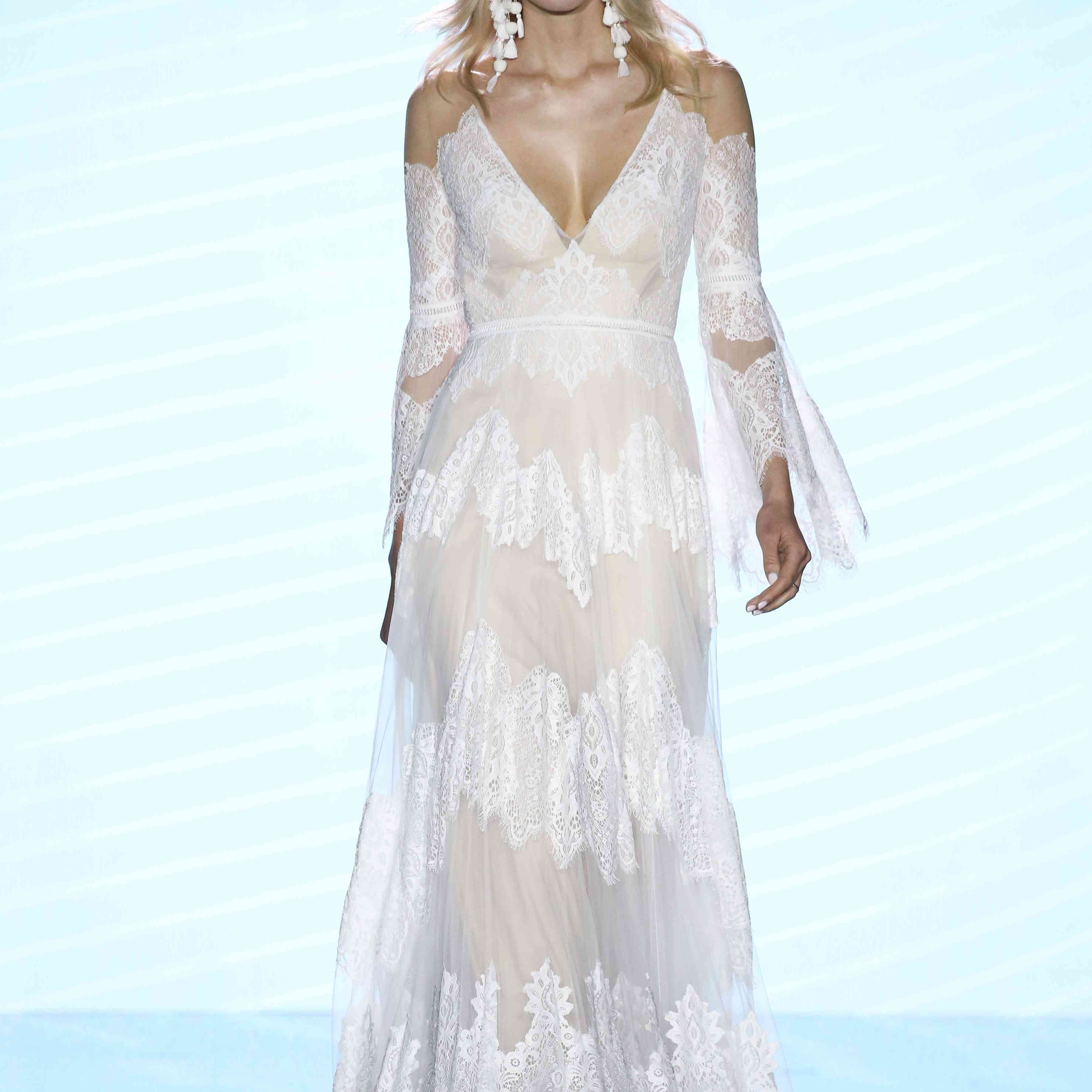 Model in lace over tulle wedding dress with cold shoulder bell sleeves and deep V-neckline
