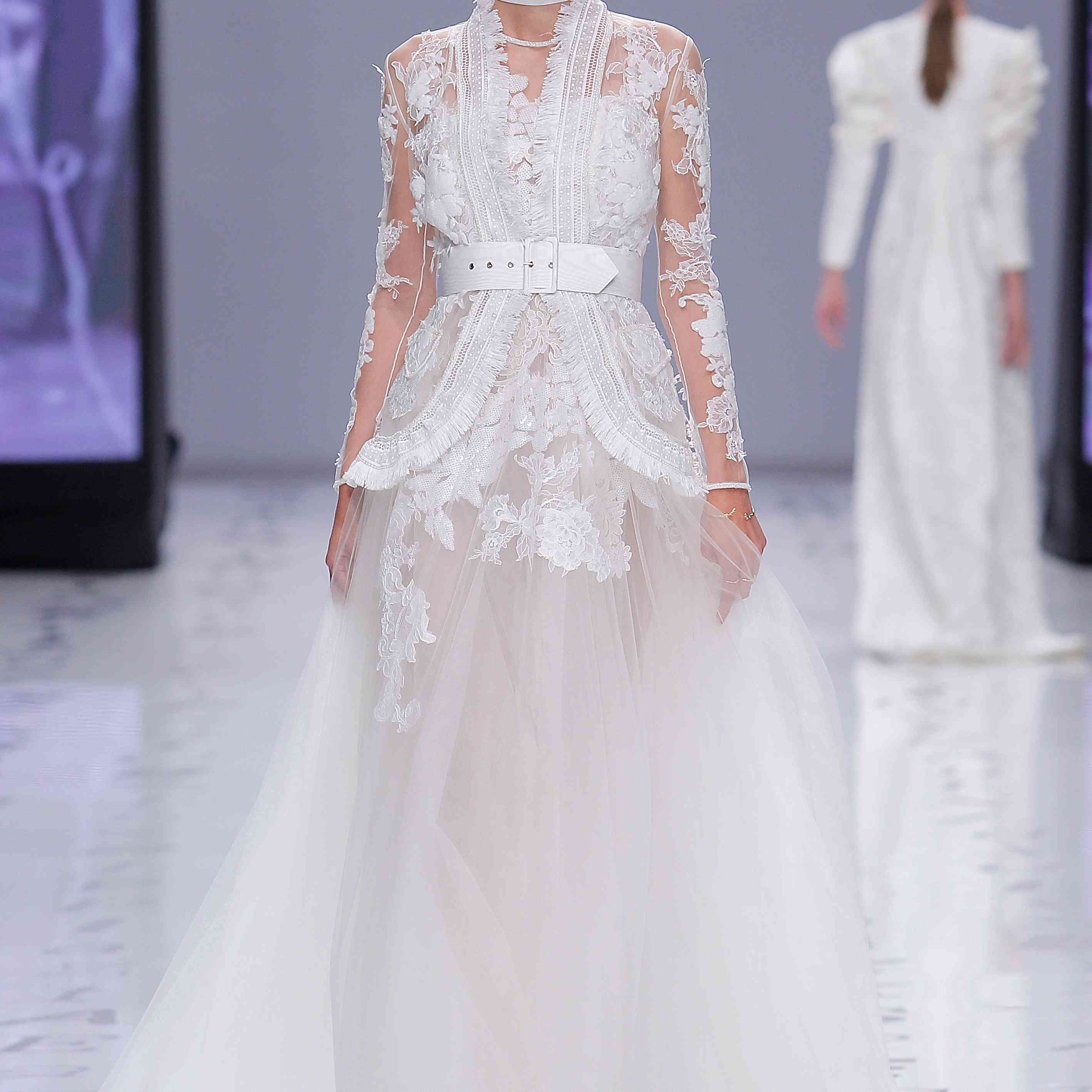 Model in a strapless princess dress with sequined embroidered lace and a chiffon skirt and a tulle jacket embroidered lace, rhinestones, and fringe, with a wide white belt at the waist