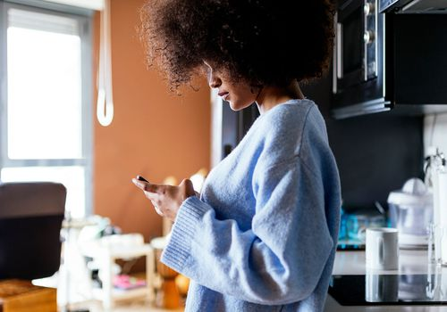 a woman in the kitchen texting