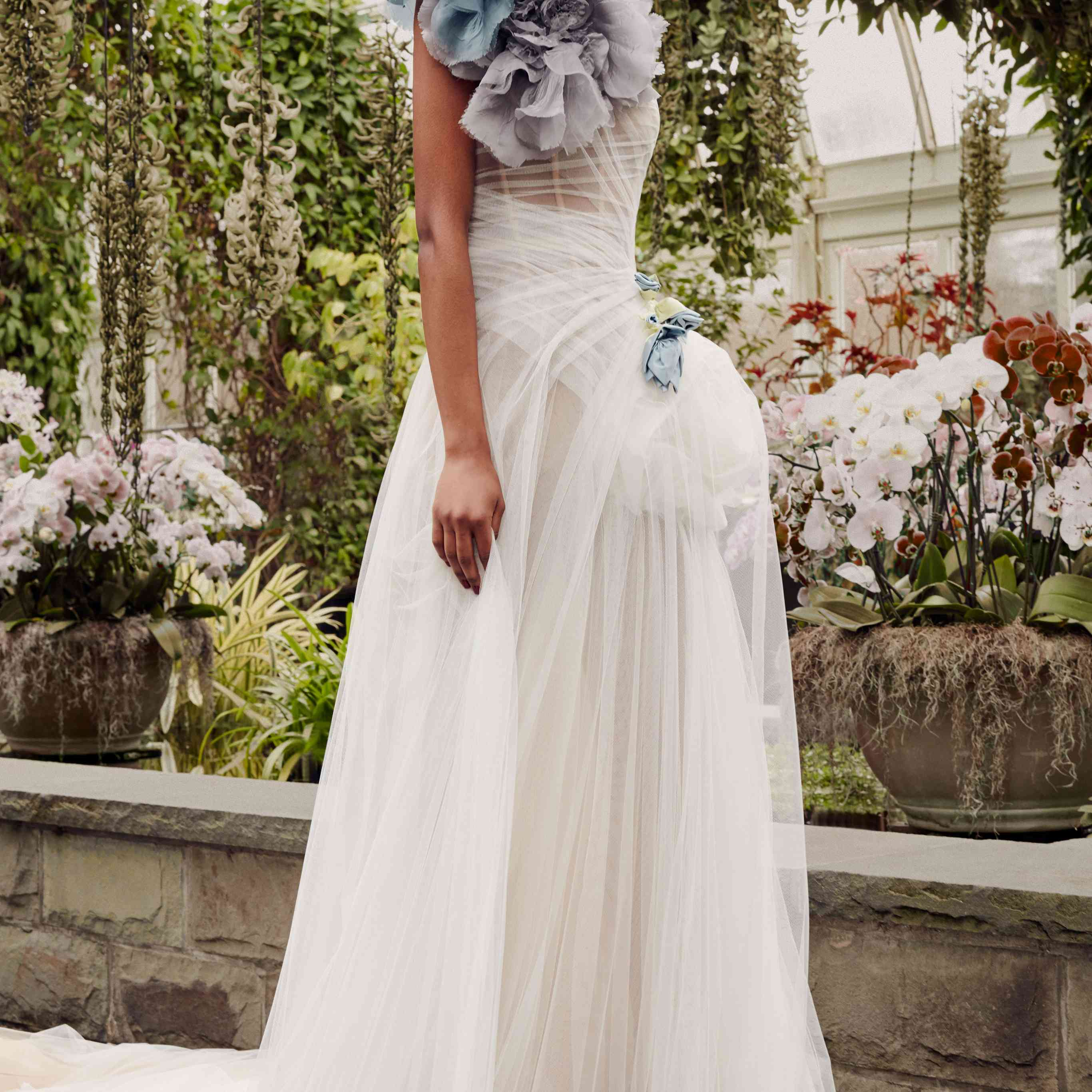 Model in sheer white tulle gown with flower accent at the waist and blue and gray flower accents at the shoulder