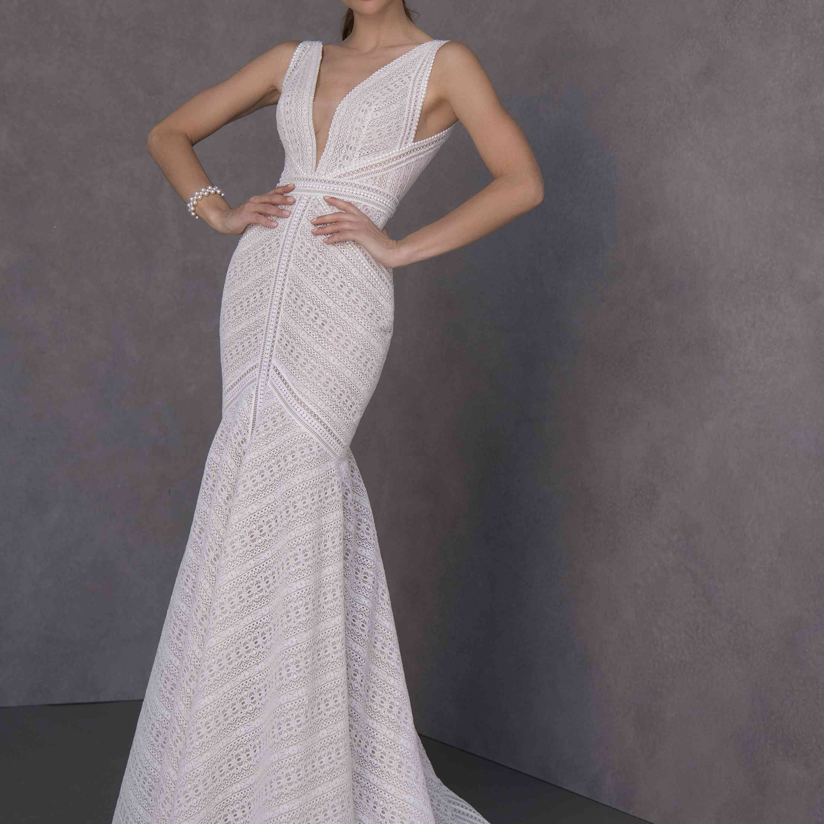 Model in geometric lace fit-and-flare gown with an illusion neckline