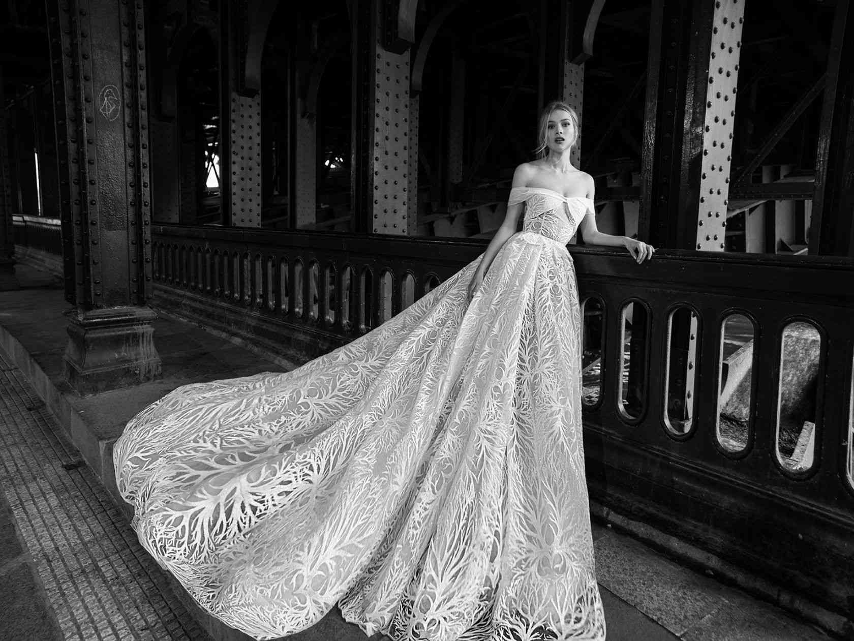 Model in off-the-shoulder ball gown with long train and embroidery on skirt