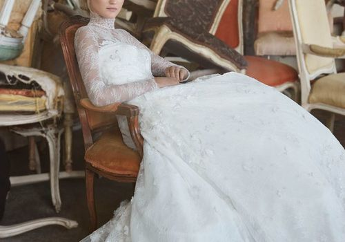 Model sitting on a chair in long-sleeve mock-neck lace wedding gown