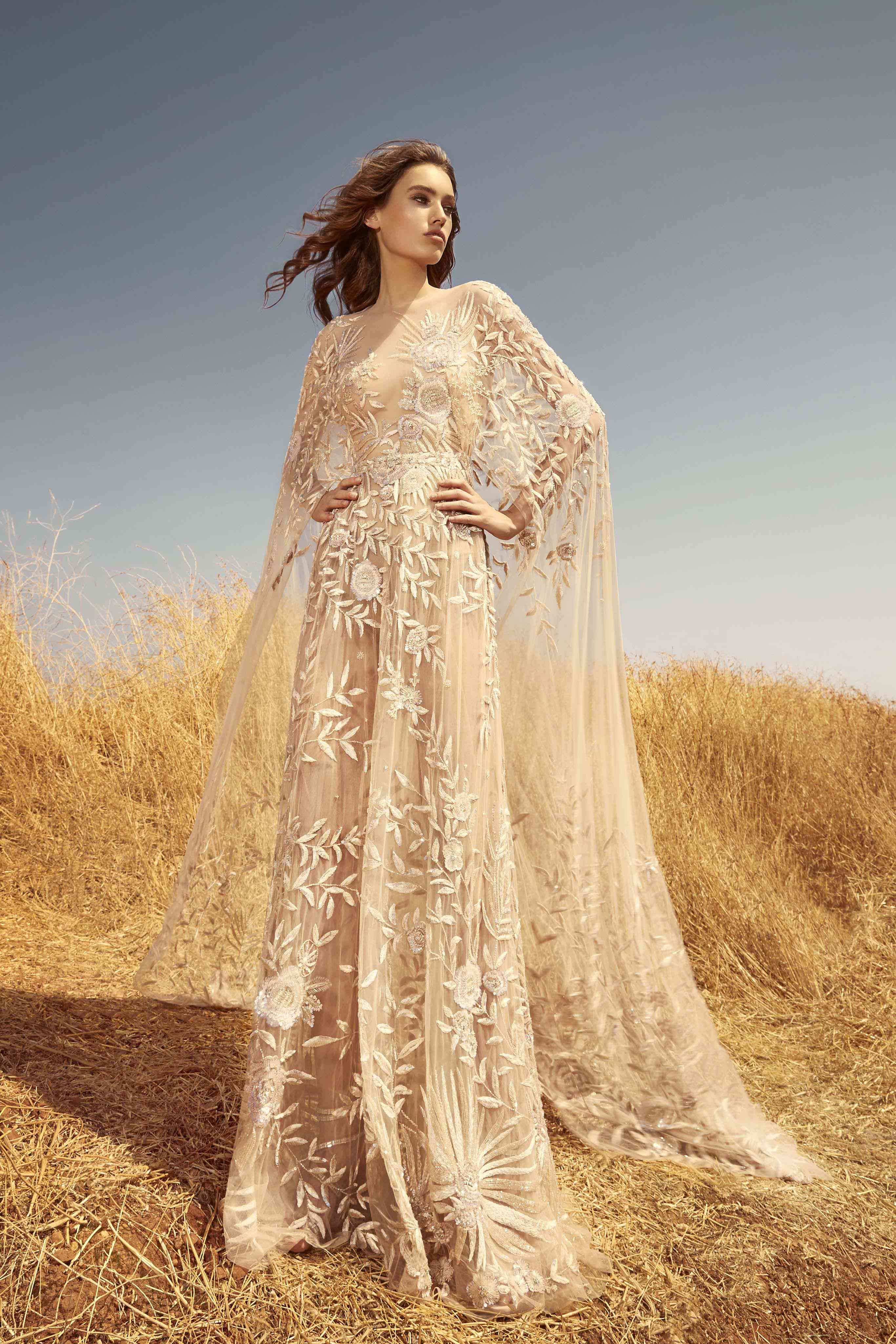 Model in an A-line fully embroidered tulle gown with an attached cape