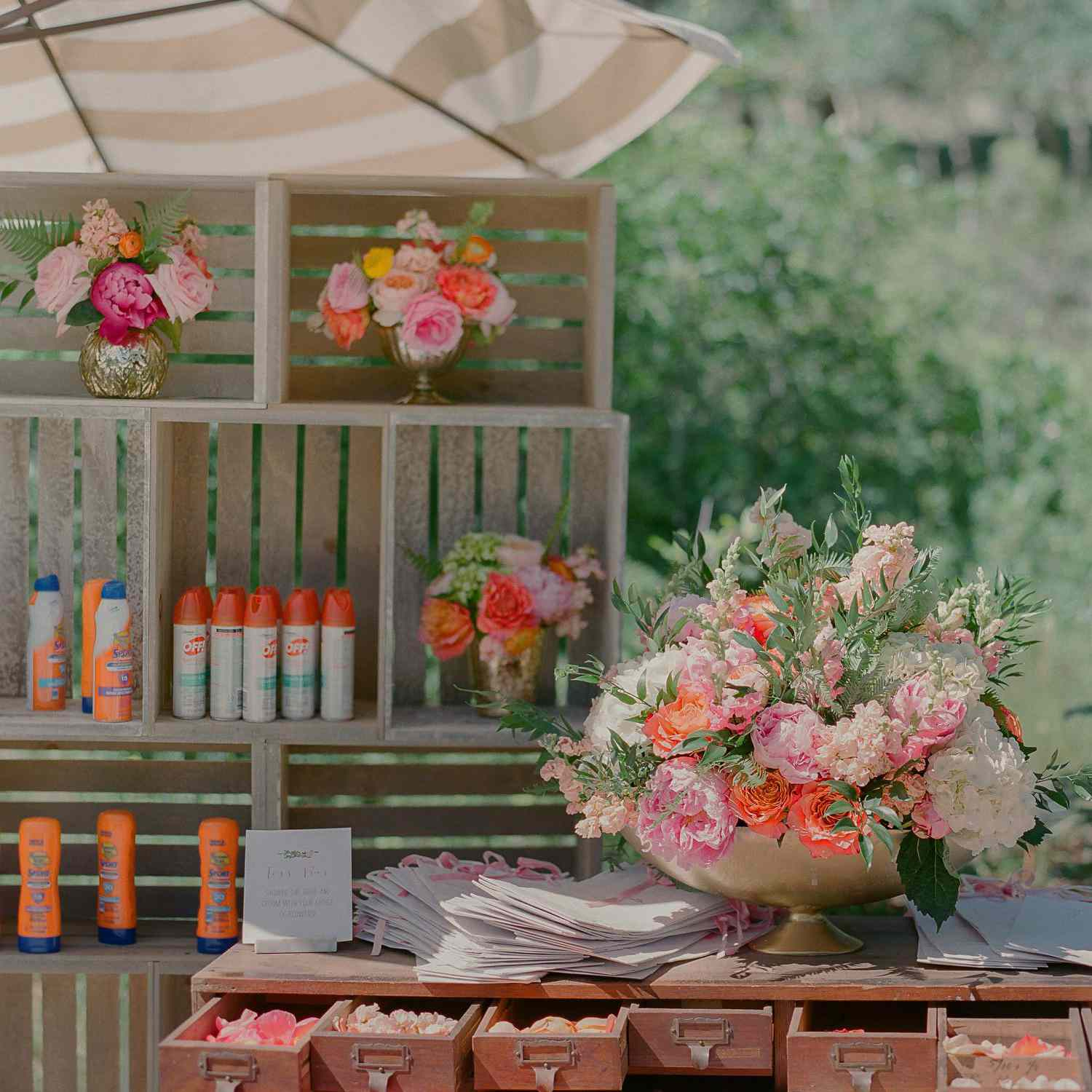 Station at a wedding with flower petal bar and wooden crates with sunscreen and bug spray