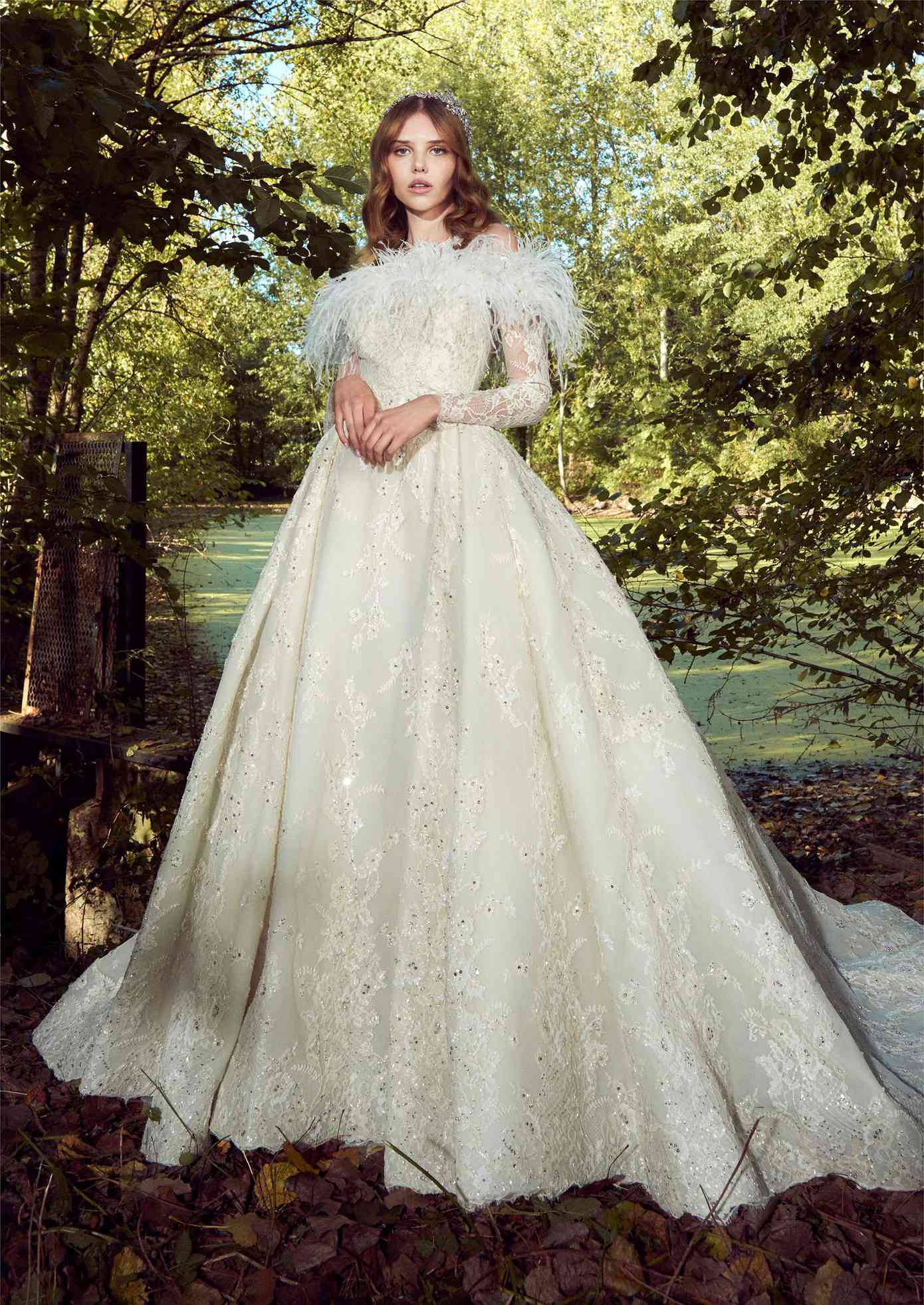 Model in an off-white high-neck sleeveless ballgown with allover sequined floral lace embroidery with a lace long-sleeve and feather pullover