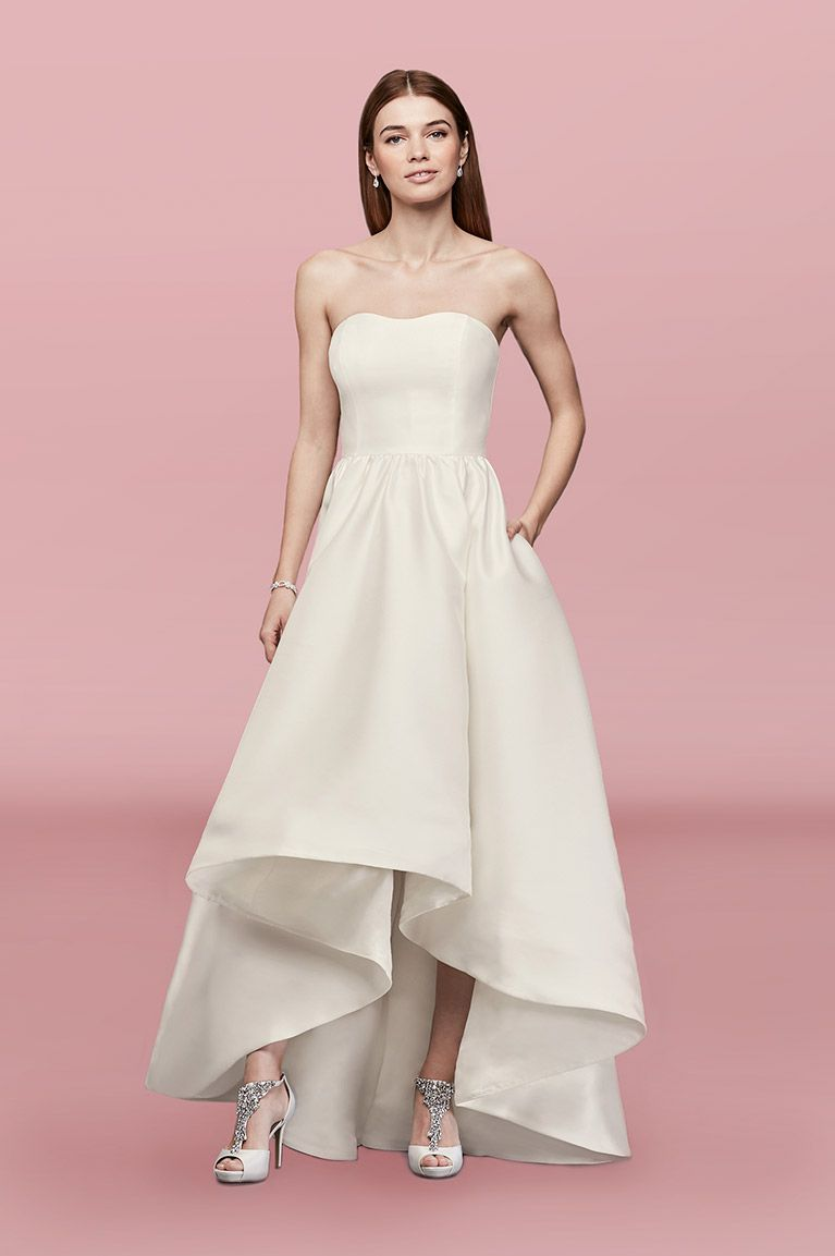 Model in strapless white wedding gown with a high-low skirt