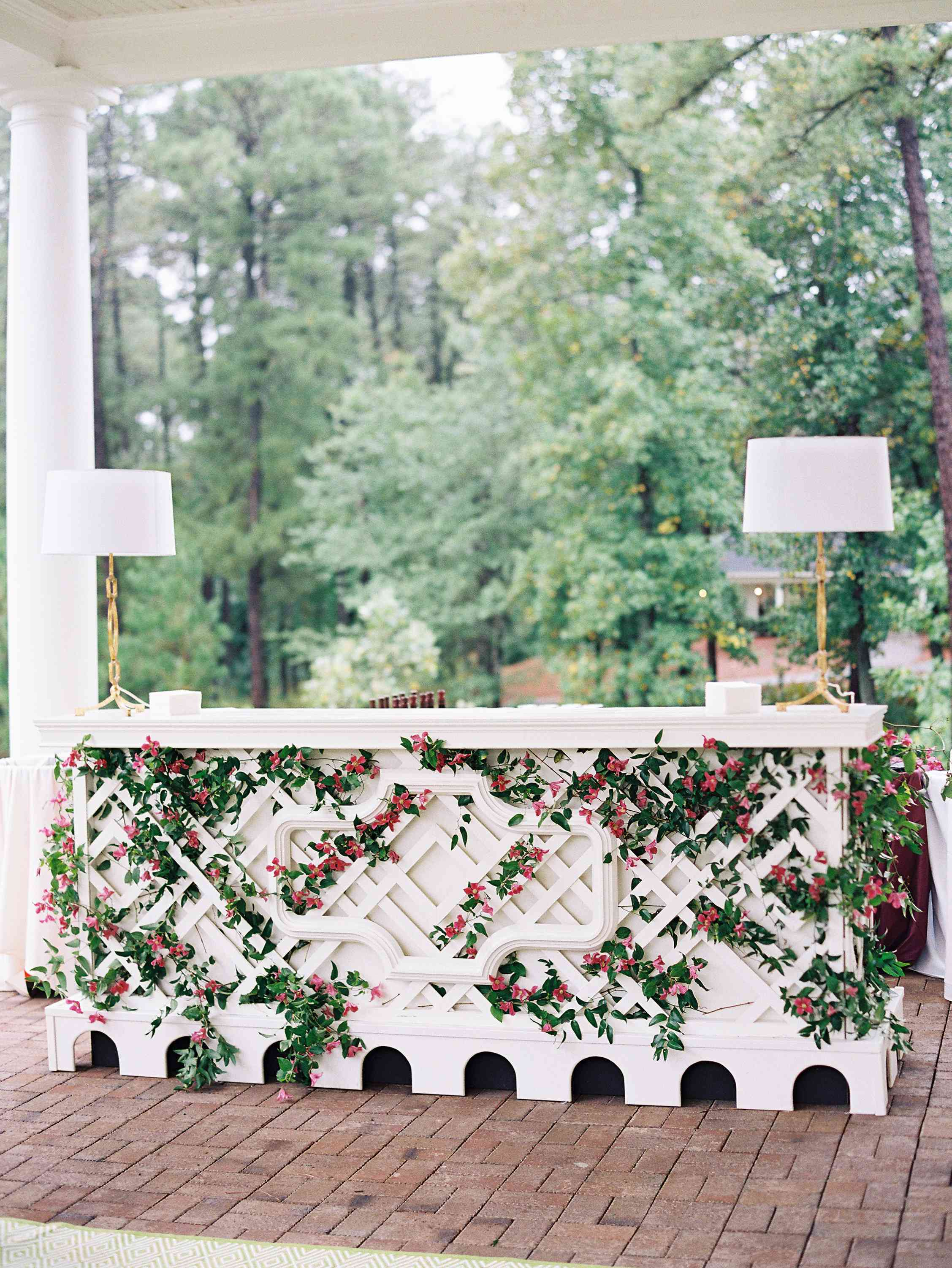 Trellis covered in floral vines with a lamp on either side
