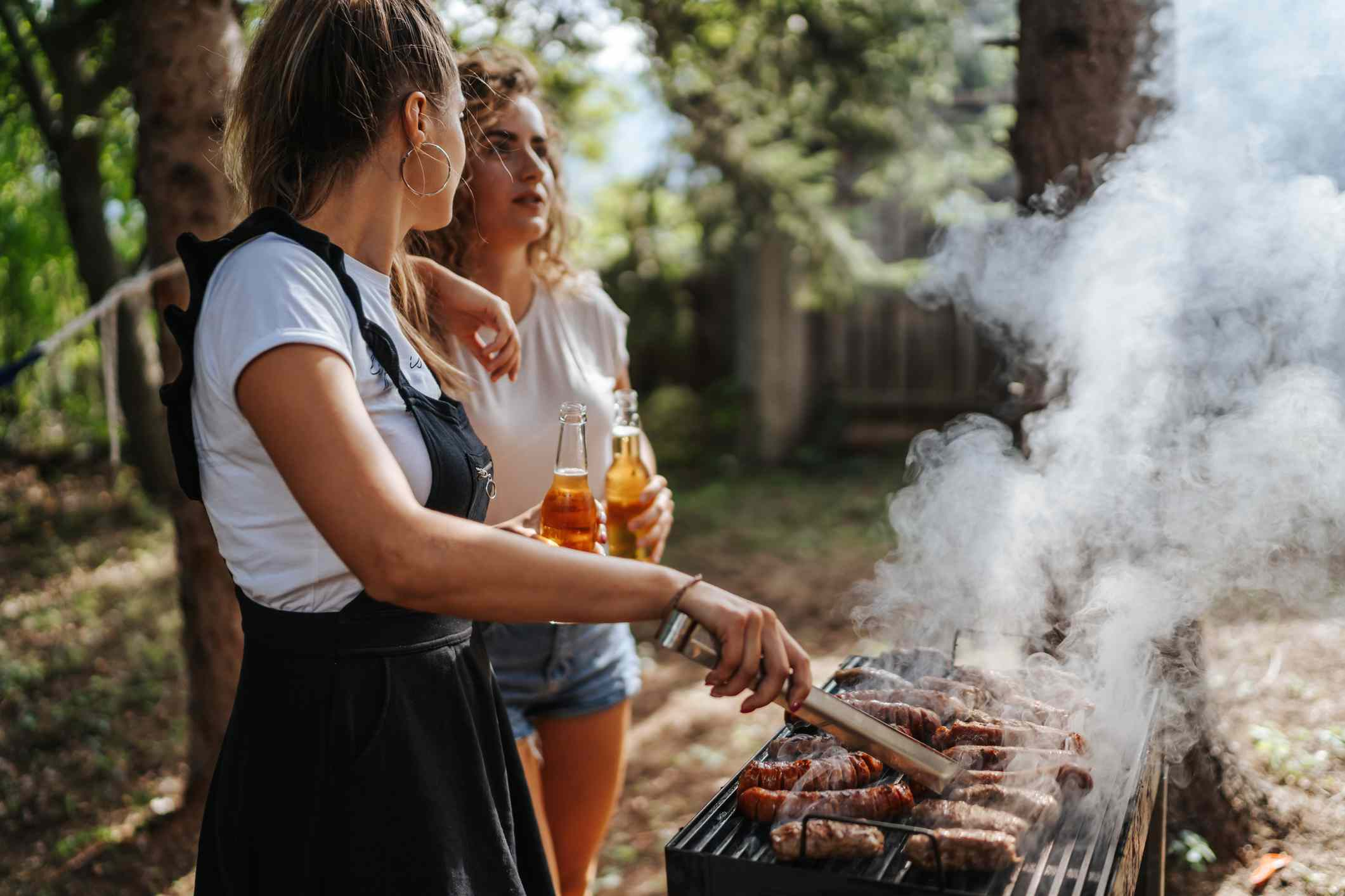 Two girls grilling and drinking beer