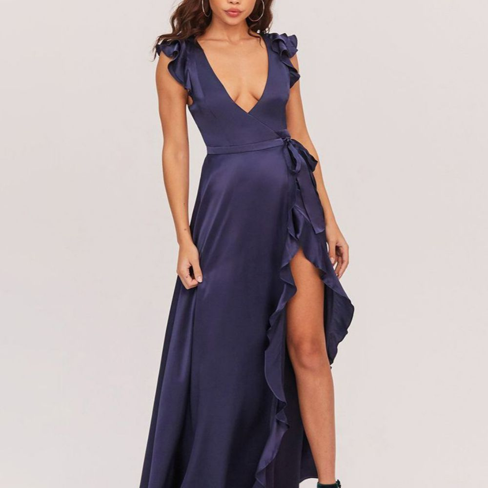 Model in a low-cut blue dress with ruffles on the sleeves and hemline and a side slit