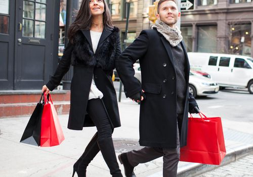 A couple walking the streets of New York City holding shopping bags
