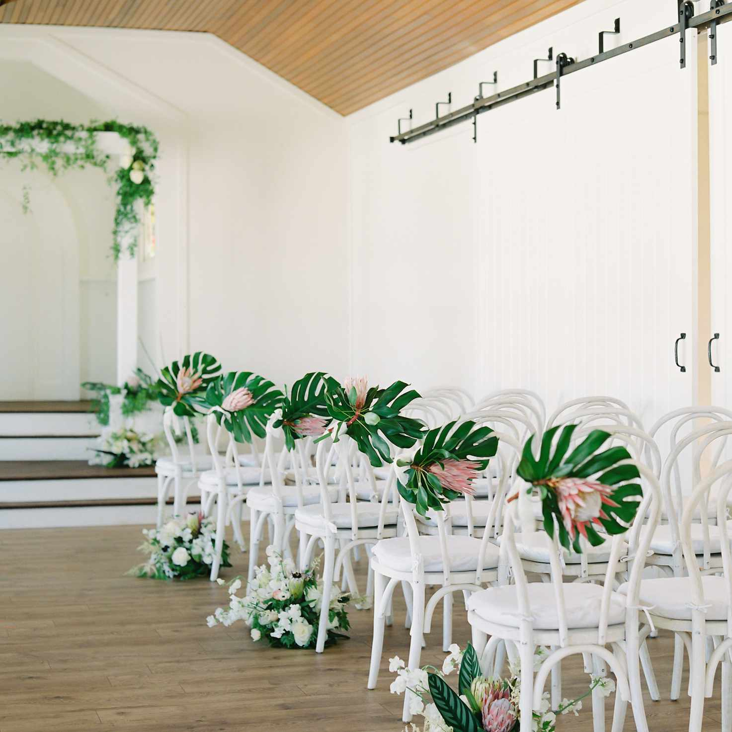 Ceremony aisle with monstera leaf and protea arrangements on chairs