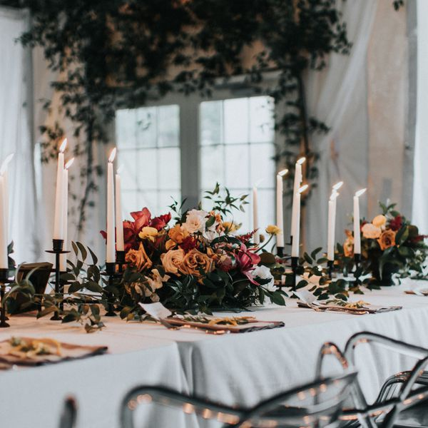 wintry table spread with white candlesticks, greenery, and roses
