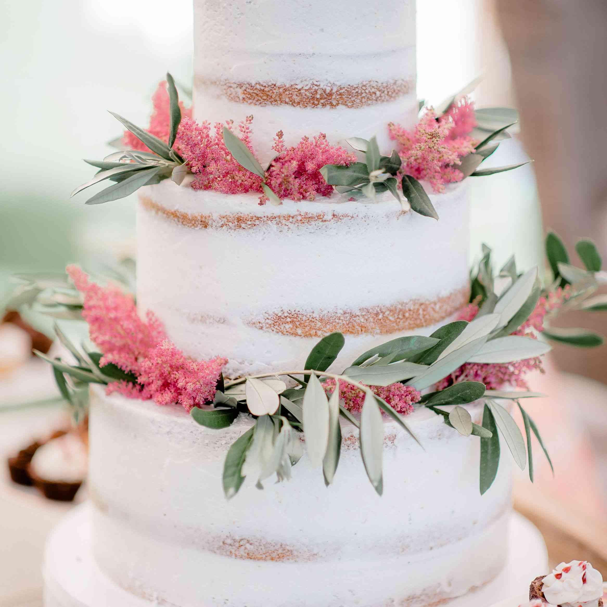 Naked wedding cake with pink flowers and greenery