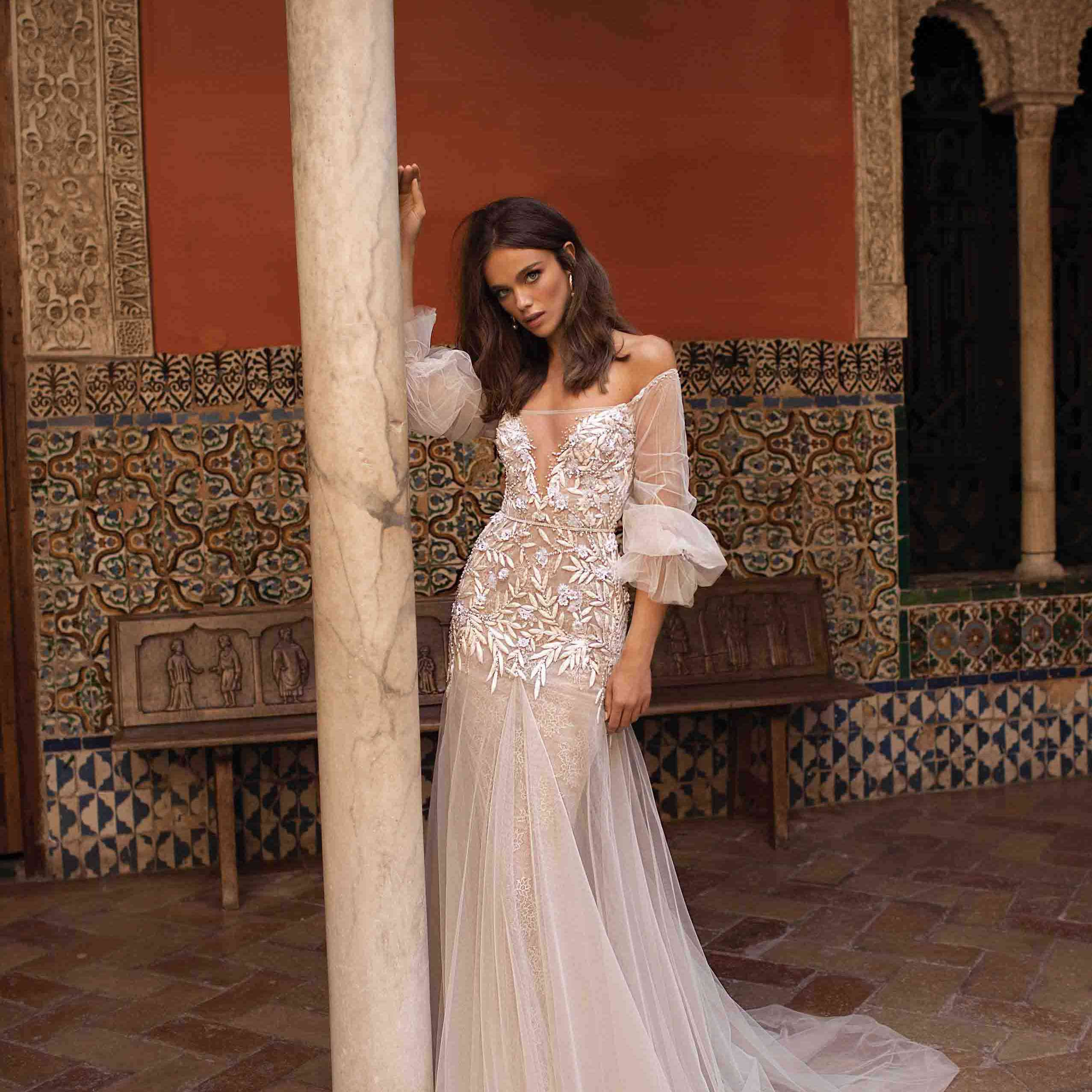 Model in illusion neckline tulle wedding gown with floral bodice and off-the-shoulder three-quarter sleeves