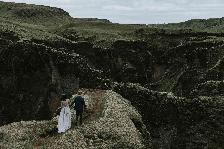 Couple walking on green ridges in Iceland