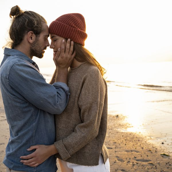 Couple embracing on beach at sunset
