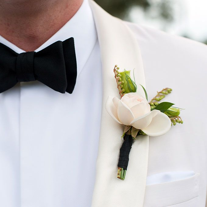 A cream rose boutonniere tied with green ribbon, created by Sara York Grimshaw Designs