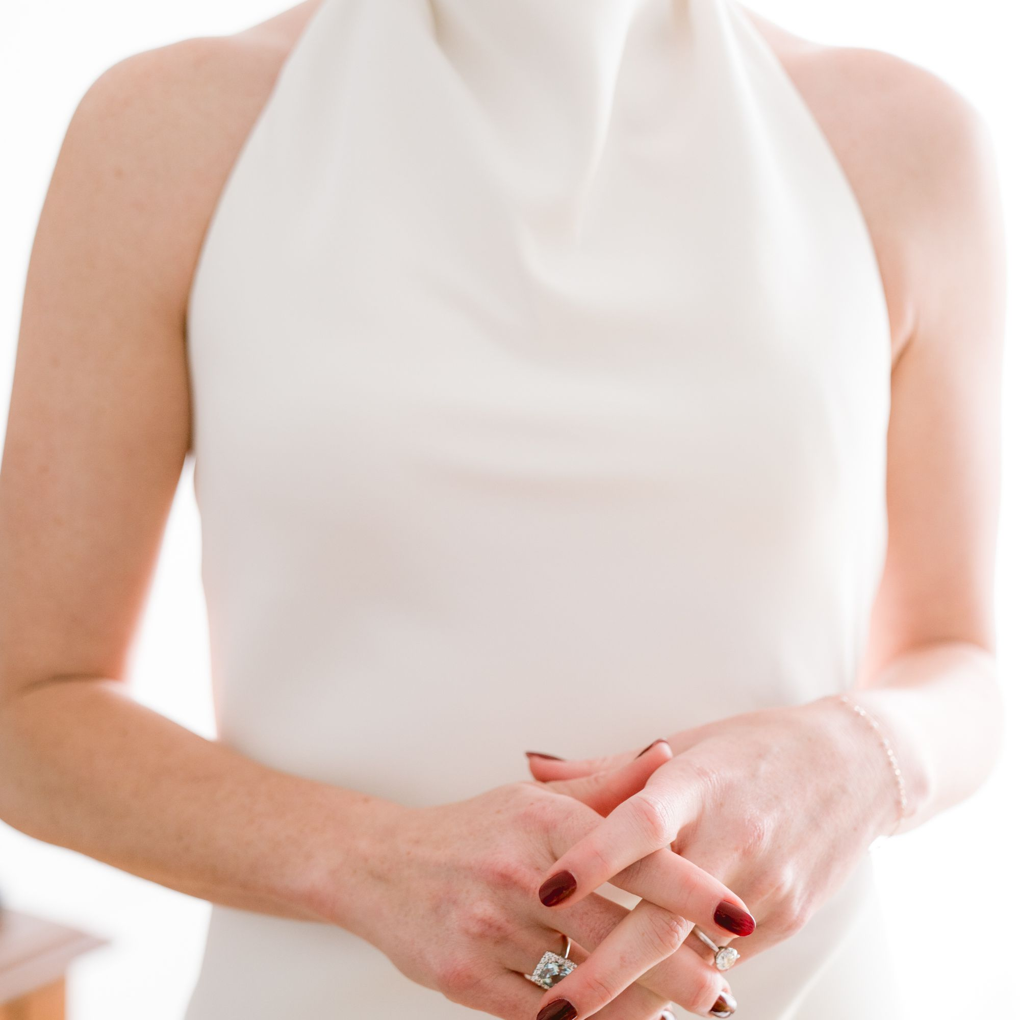 Bride in a sleeveless white gown with her hands together wearing burgundy nail polish