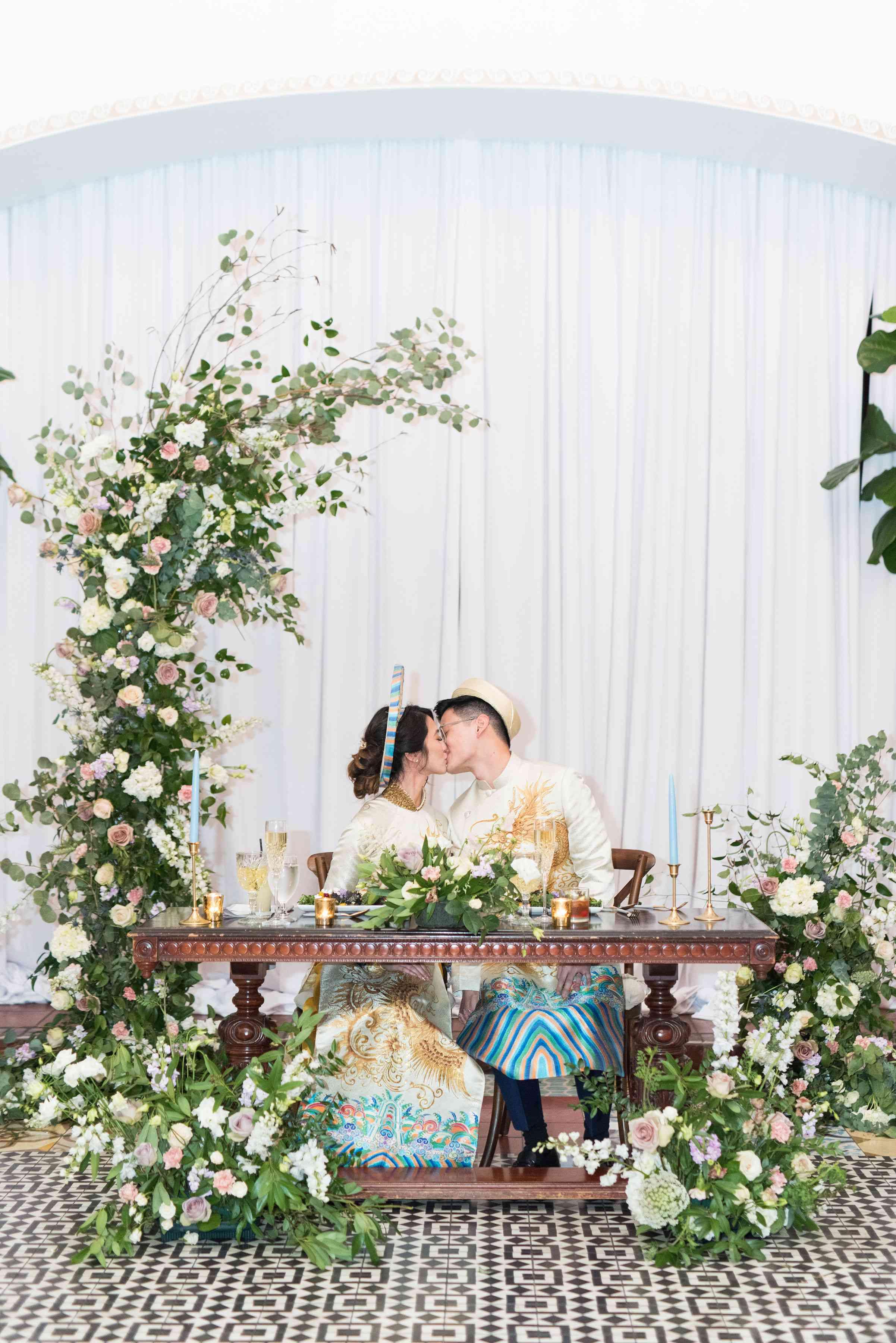 newlyweds kissing at table
