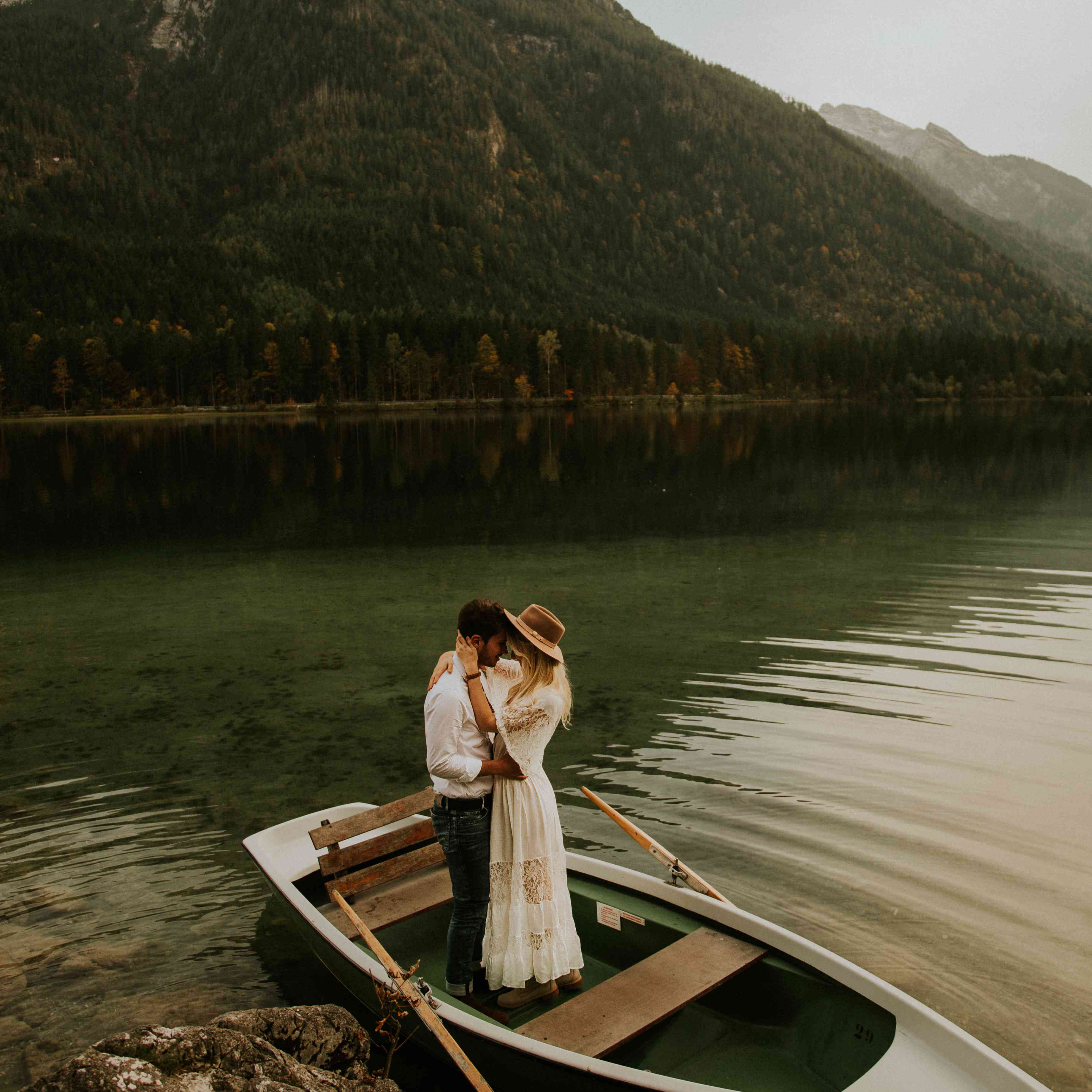Couple kissing in a boat on a mountainside lake