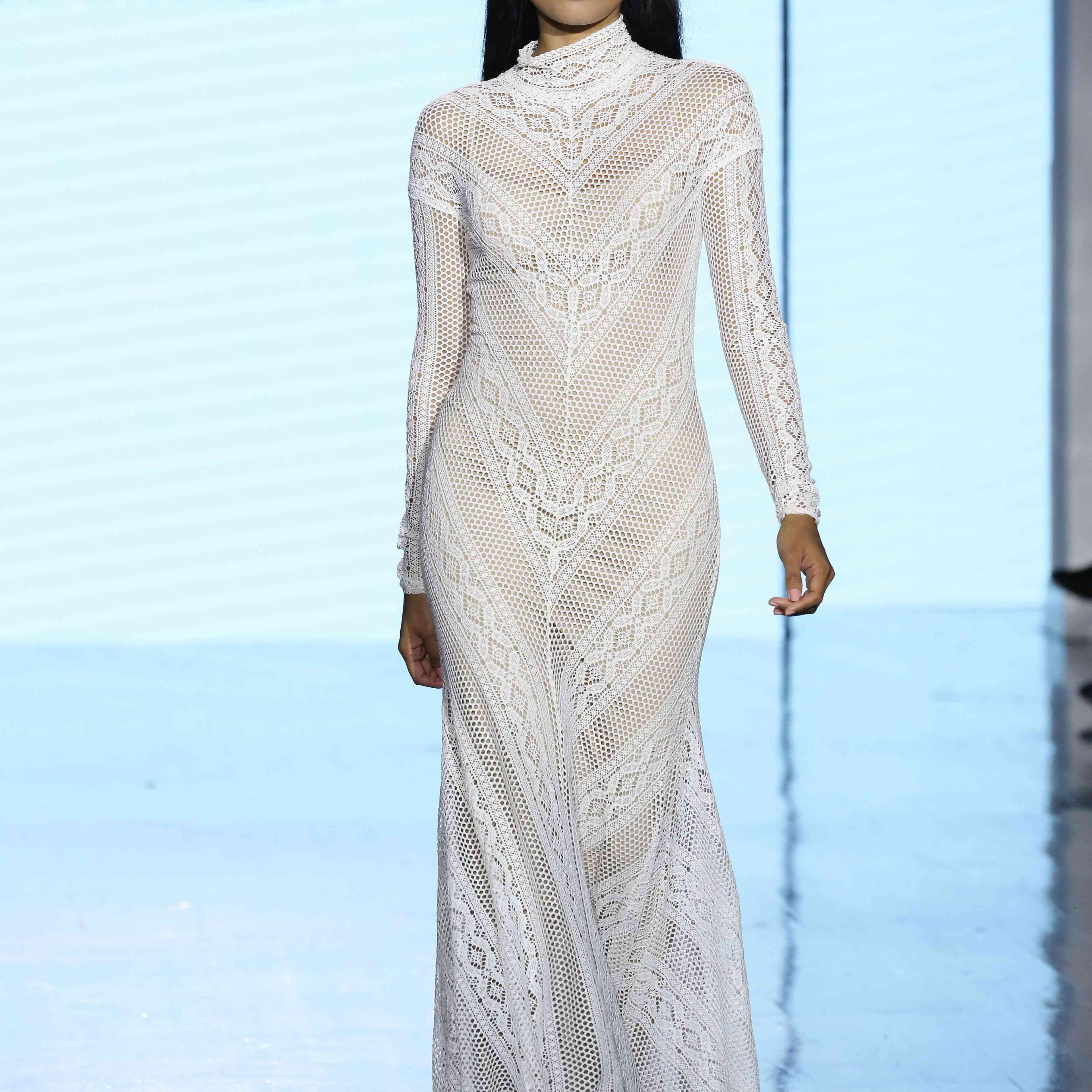 Model in long-sleeve high-neck sheer lace wedding dress