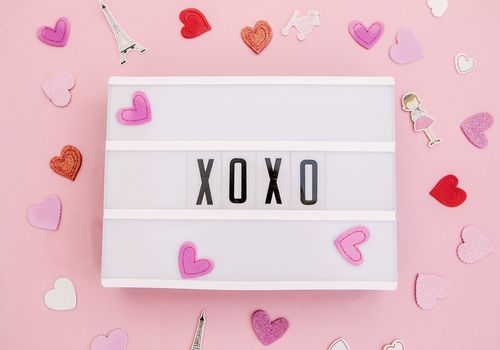 xoxo on a letterboard with pink and white hearts all around
