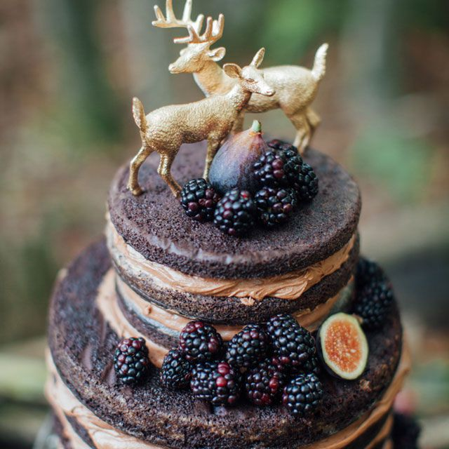 Naked chocolate cake with blackberries and gold deer