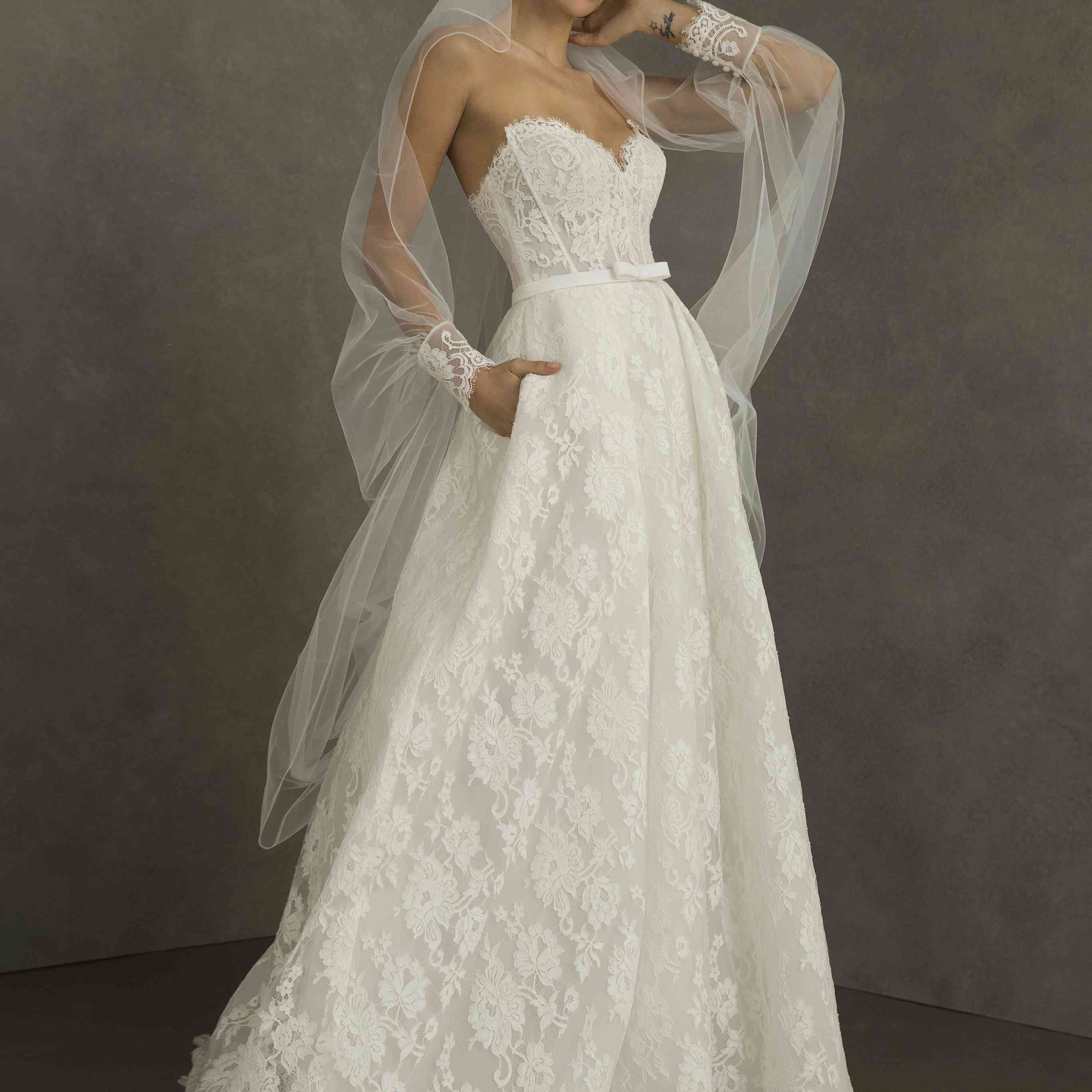Model in strapless lace sweetheart ballgown with a thin waistband with a small bow detail