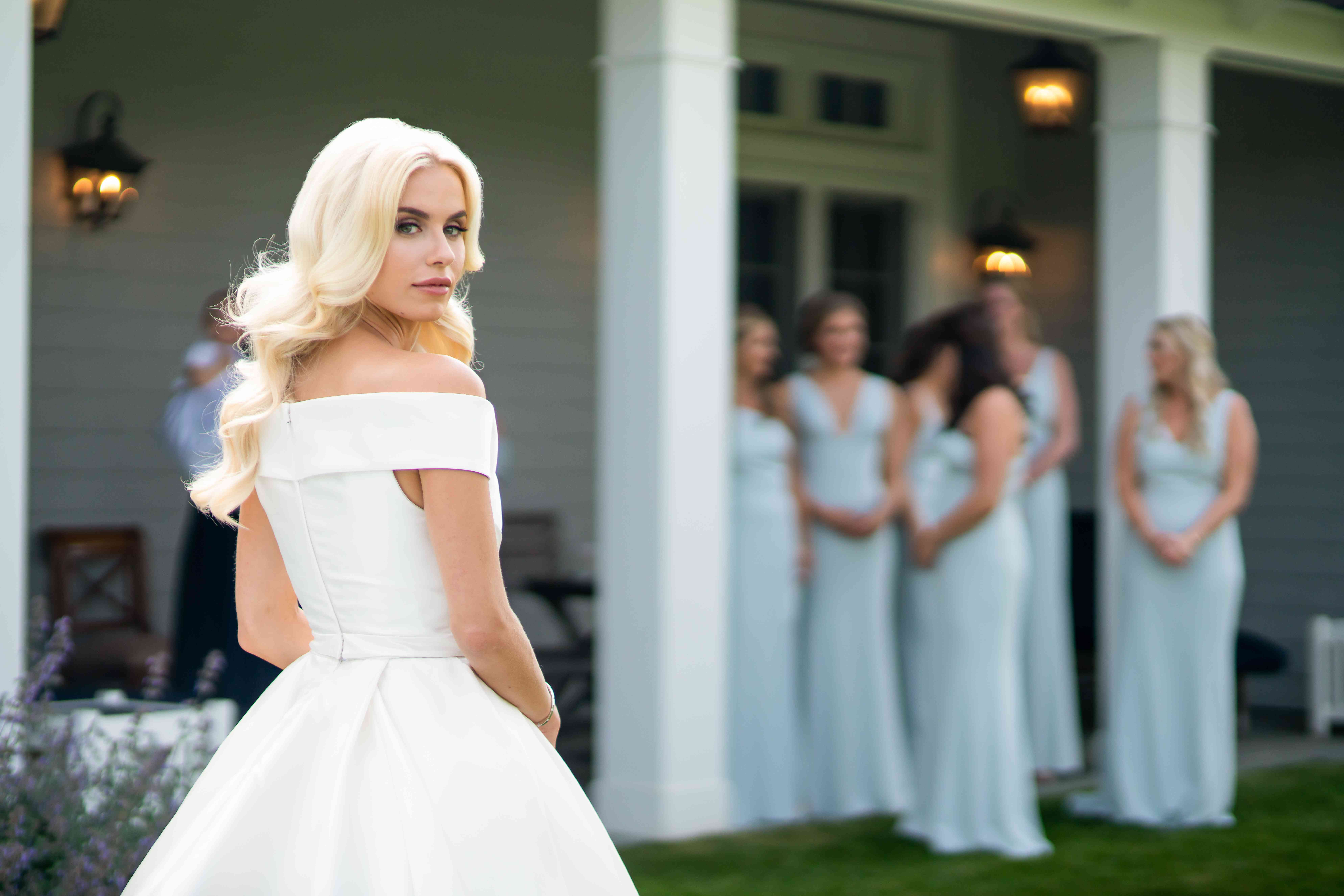 Bridal portrait with bridesmaids in the background
