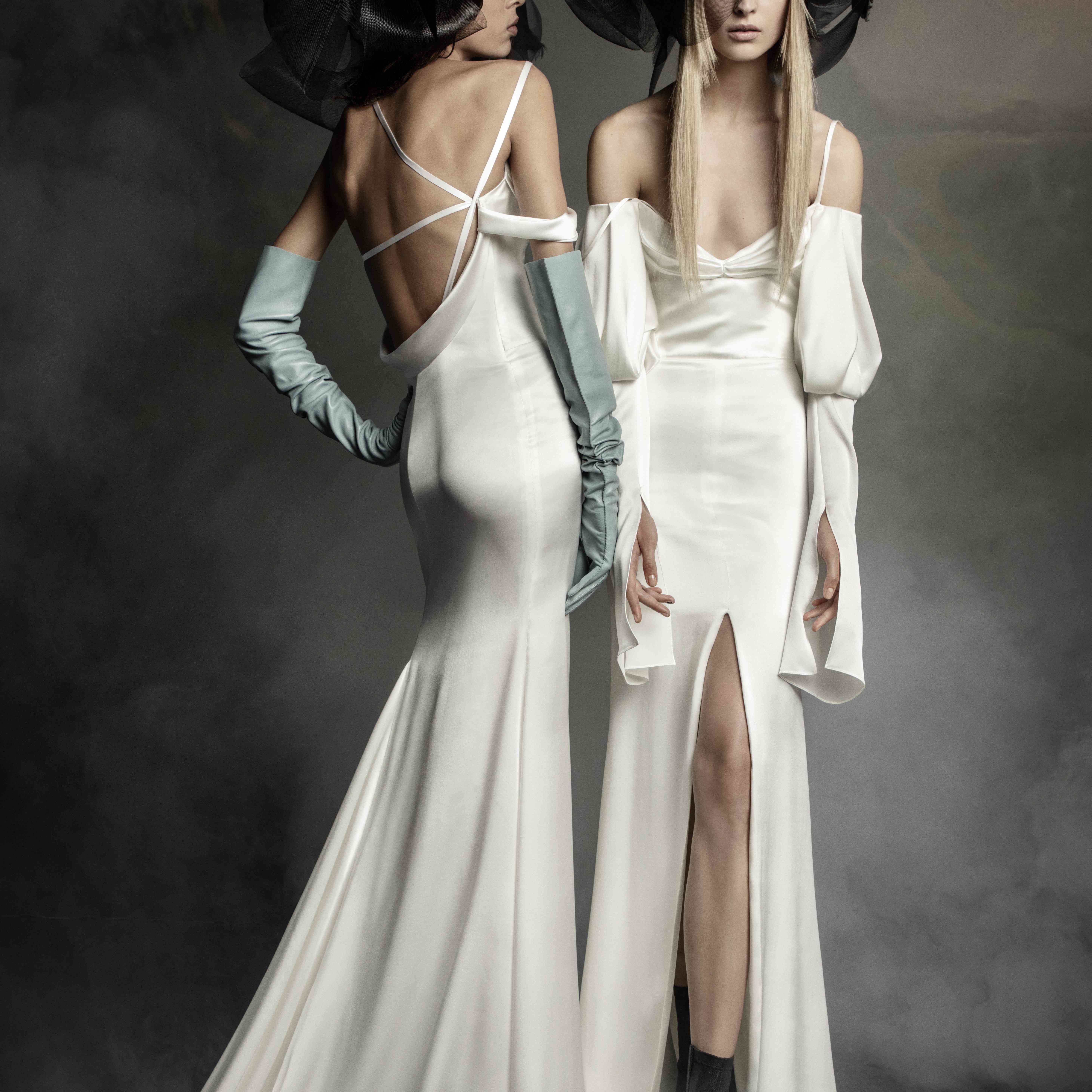 Two models in off-the-shoulder fit and flare gowns with strappy sleeve detail and black headpieces