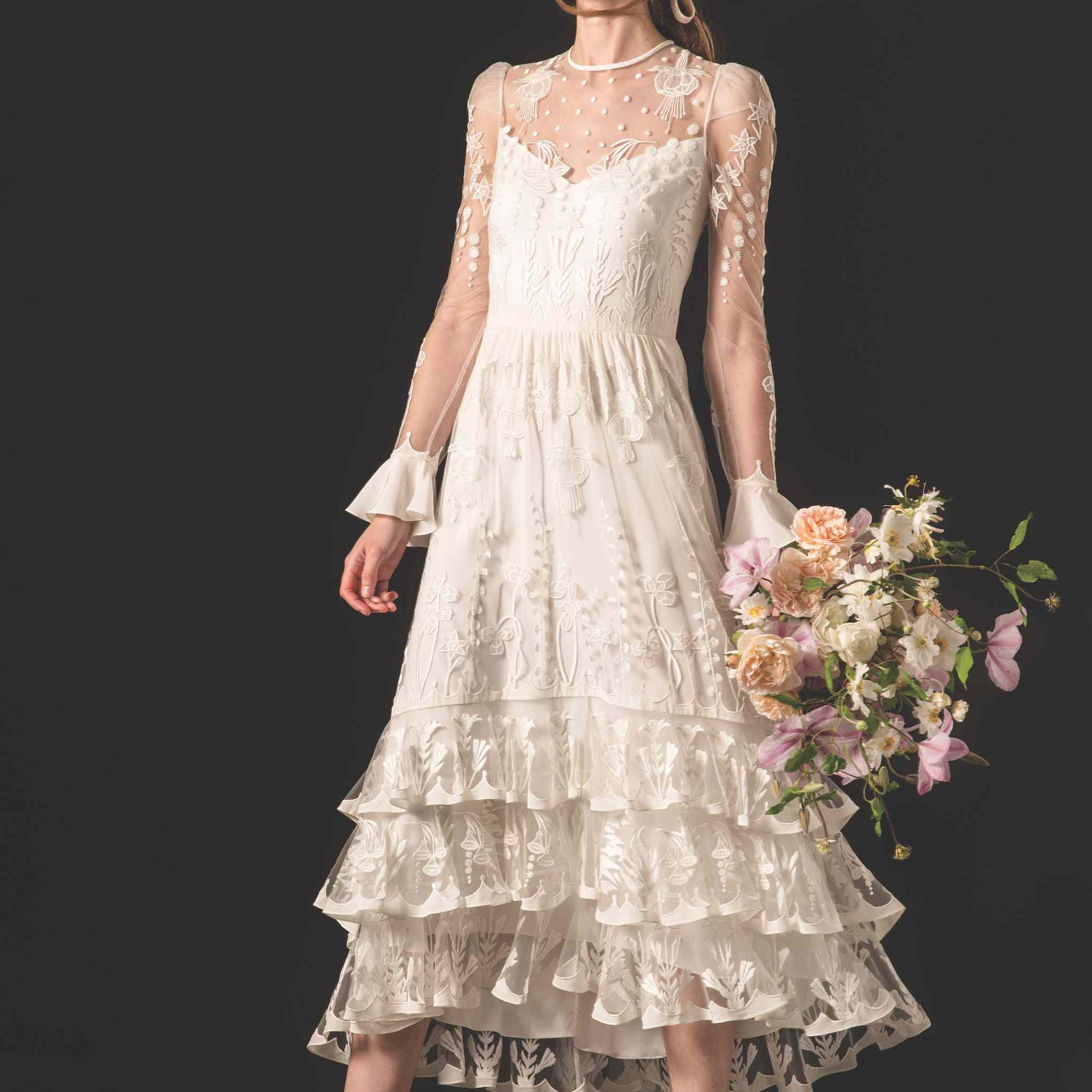 Model in tea-length embroidered tulle dress with long sleeves and ruffles
