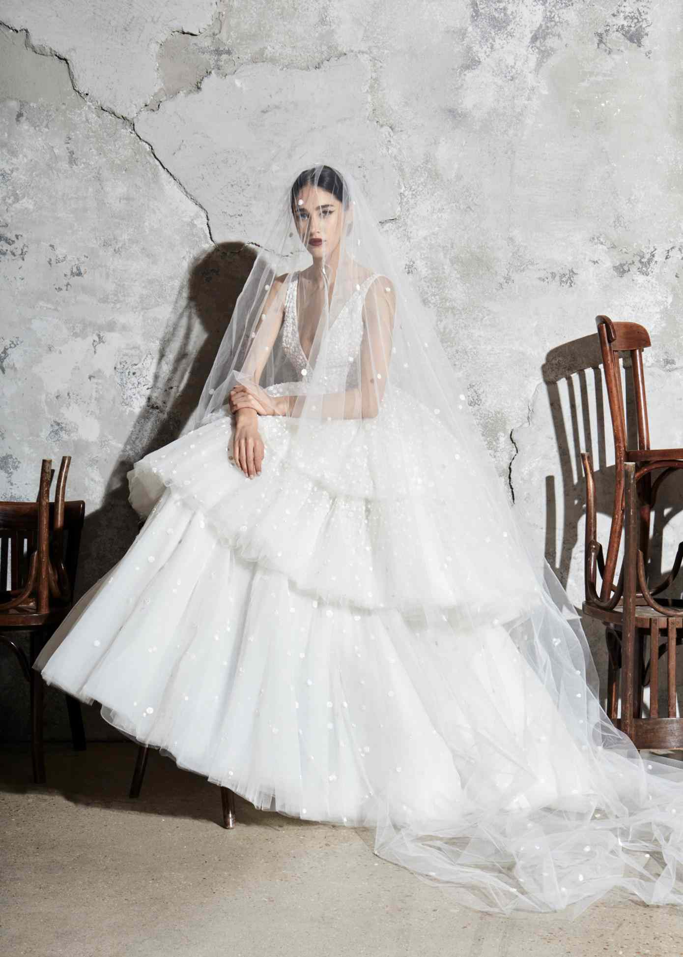 Model in a V-neck sequined tulle ballgown with a three-tiered skirt and a matching sheer tulle veil