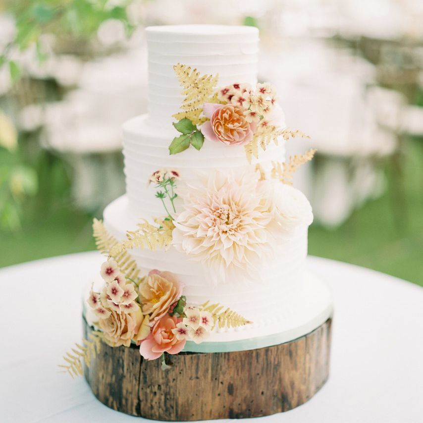 White tiered wedding cake with leaves and floral accents