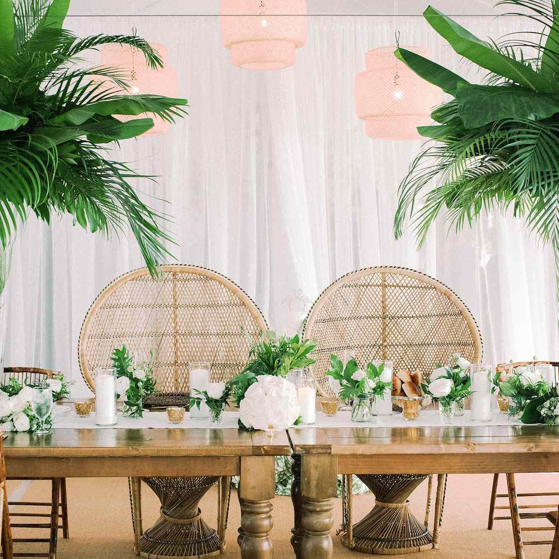 Rattan peacock sweetheart chairs in front of reception table
