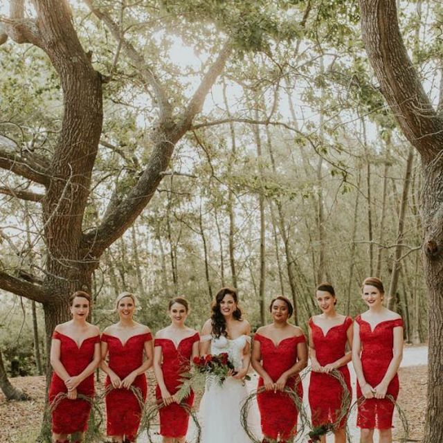 Bridesmaids in red dresses holding greenery wreaths