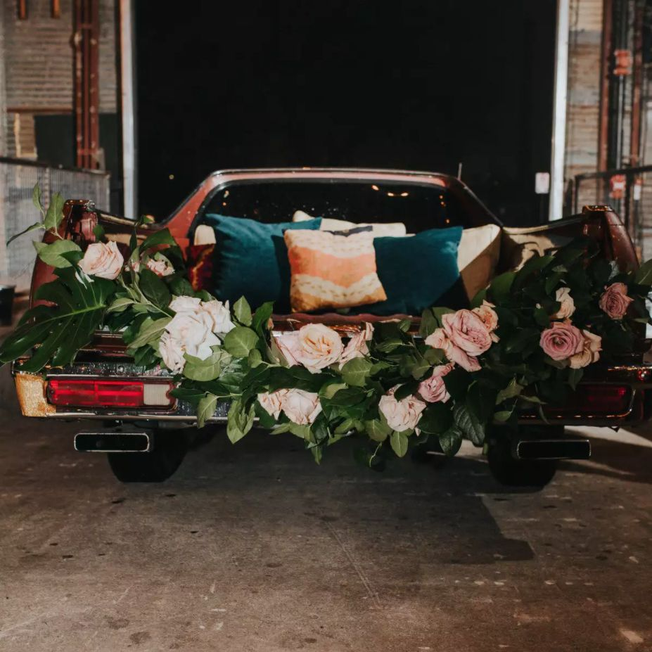 Vintage El Camino decked out with blankets, pillows, and a garland of roses