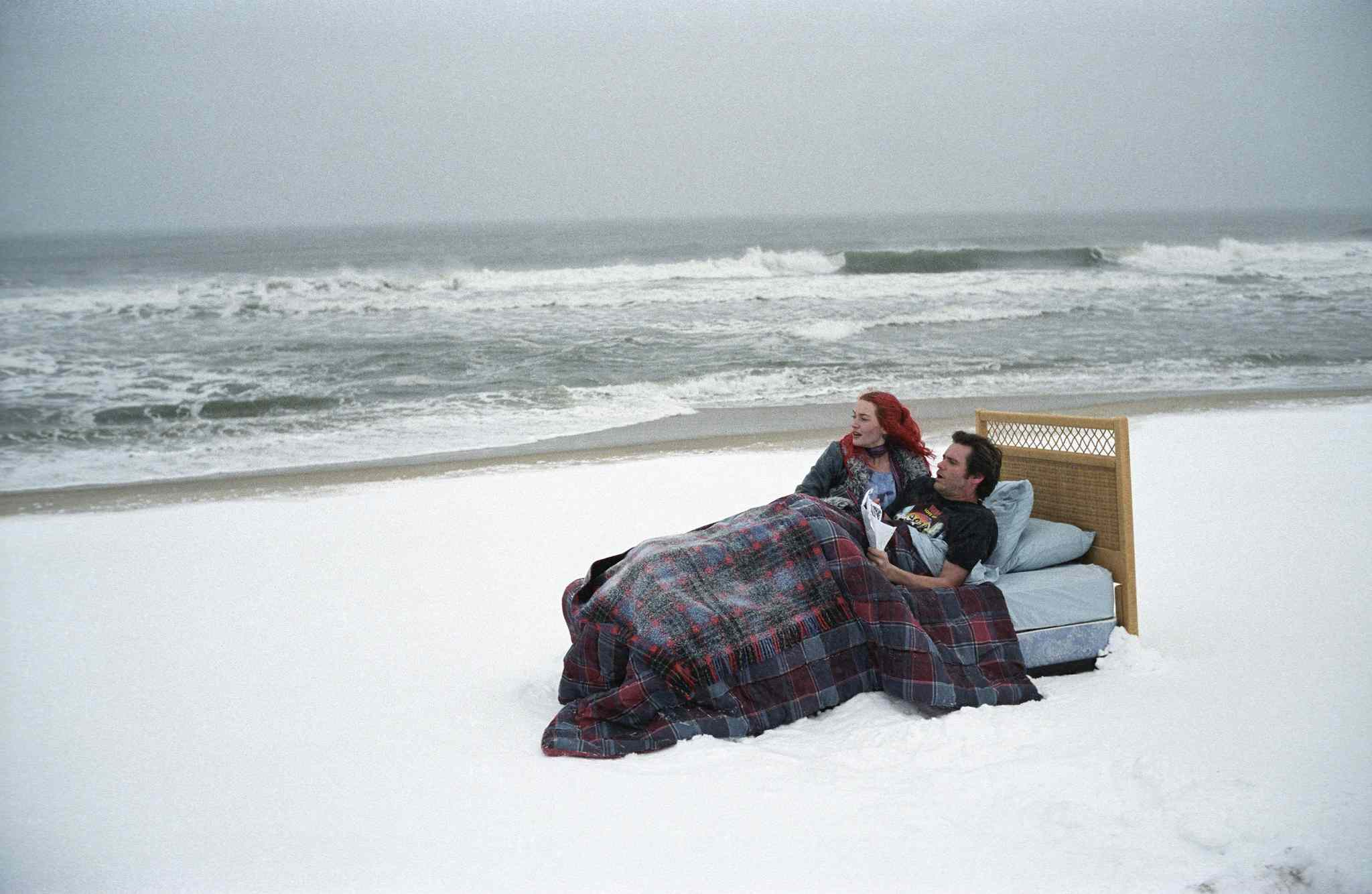 Jim Carrey and Kate Winslet wake up in a bed on the beach, still from